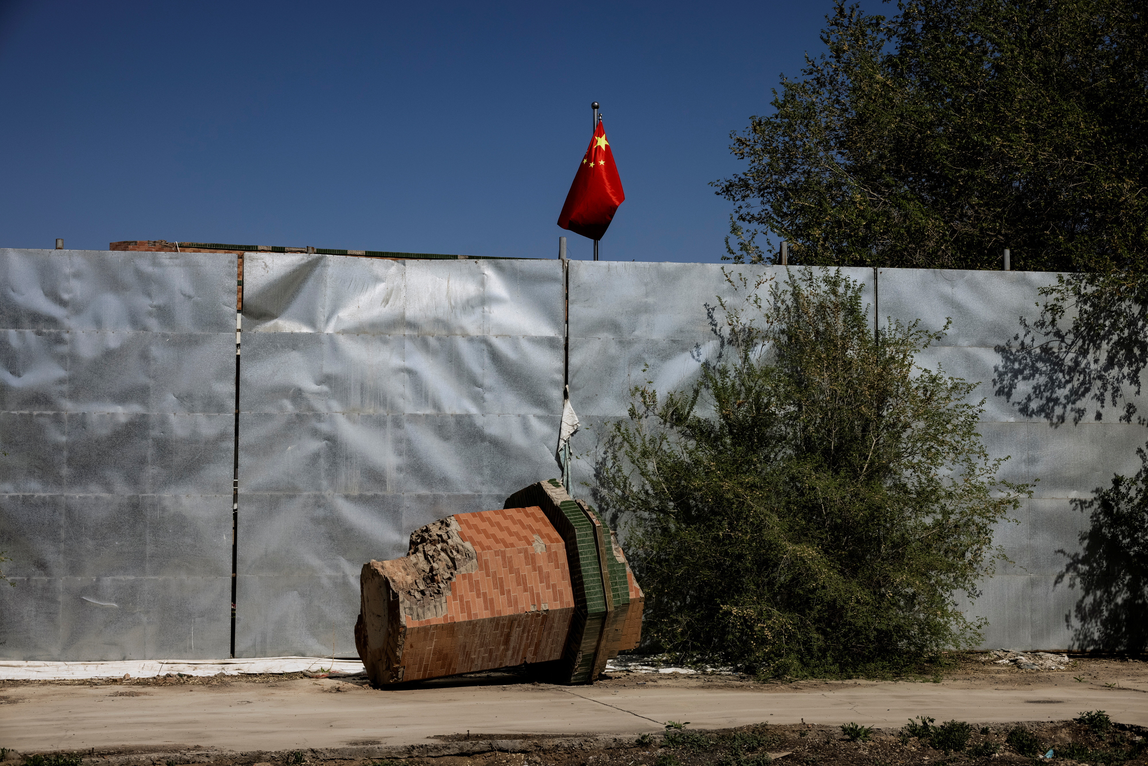 A part of a minaret broken off from the former Xinqu Mosque lies near a Chinese national flag in a yard adjacent to the former house of worship in Changji outside Urumqi, Xinjiang Uyghur Autonomous Region, China, May 6, 2021. Picture taken May 6, 2021.  REUTERS/Thomas Peter