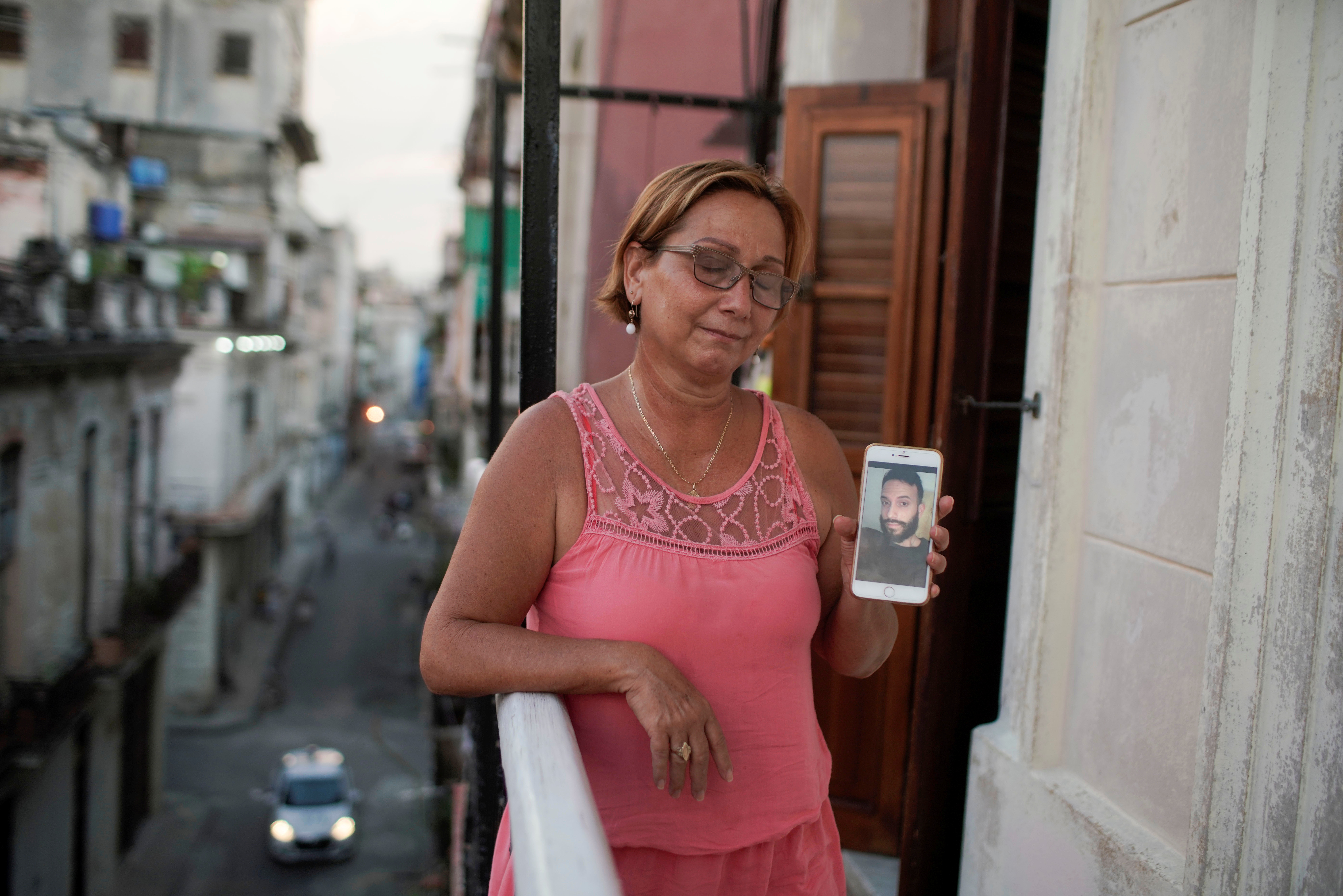 Raisa Gonzalez reacts as she shows a picture of her son Angelo Troya Gonzalez, an artist sanctioned after protests, in Havana, Cuba, July 20, 2021. REUTERS/Alexandre Meneghini