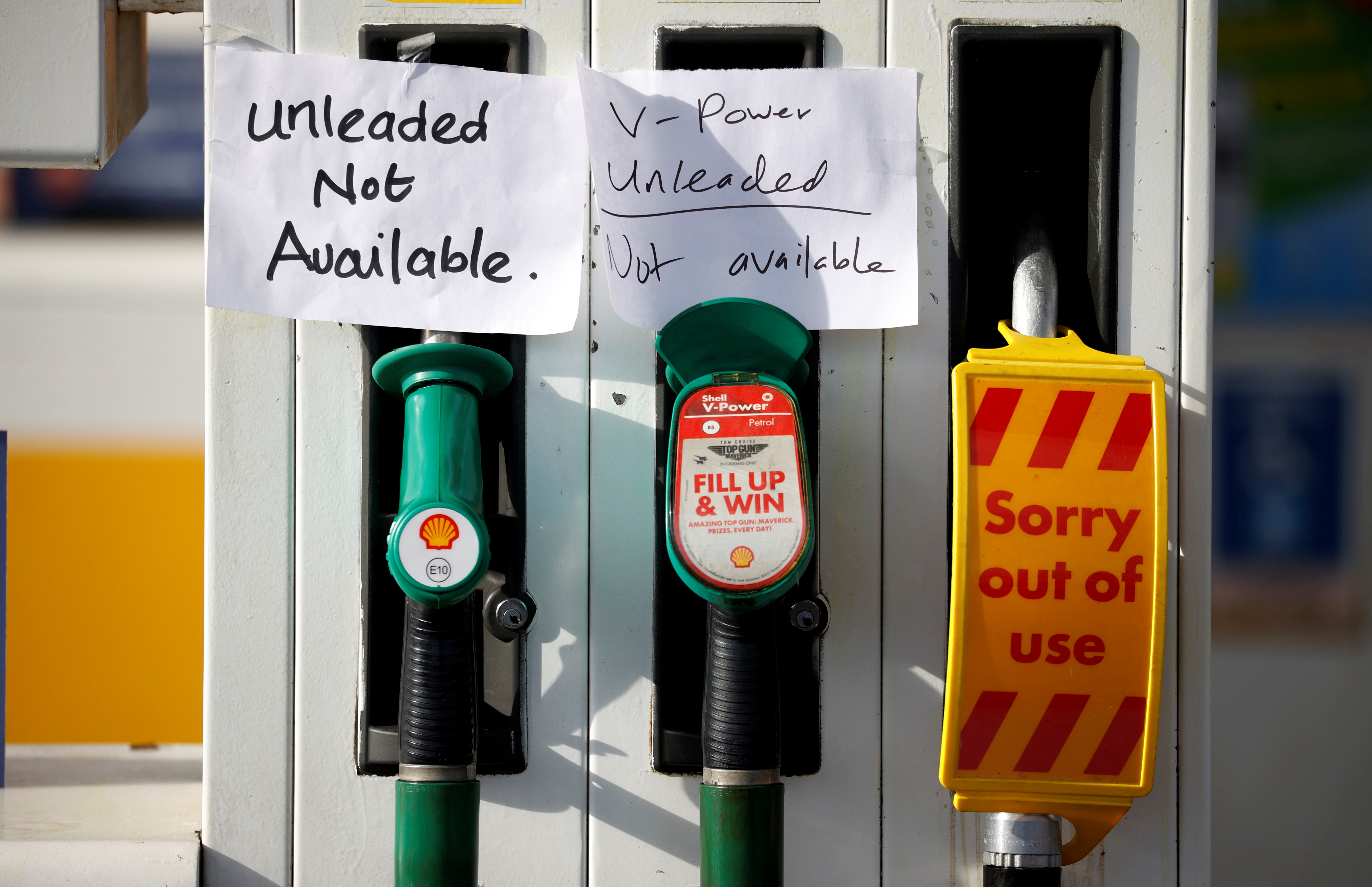 Hand written signs are stuck to a petrol pump with no fuel available at a Shell filling station in Manchester, Britain, September 24, 2021. REUTERS/Phil Noble/File Photo