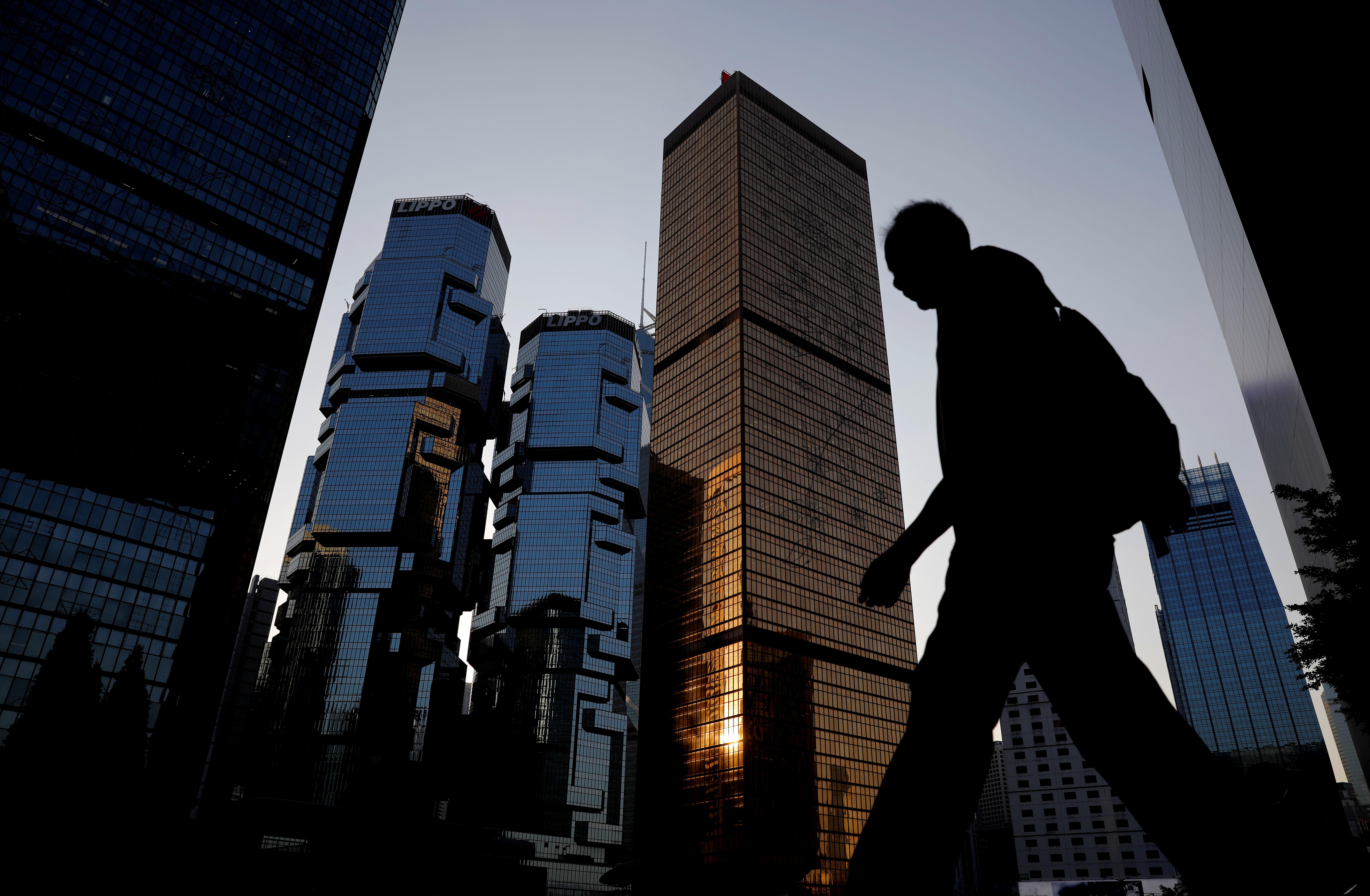A man walks past buildings at a business district in Hong Kong, China, November 4, 2019. REUTERS/Kim Kyung-Hoon