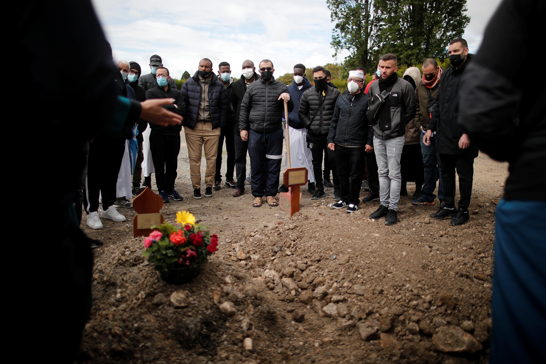 Волонтерите на здружението Тахара се молат за 38-годишниот Абукар Абдулахи Каби, муслимански бегалец, кој почина од коронавирусна болест (КОВИД-19), за време на погребната церемонија на гробиштата во Ла Курнев, во близина на Париз, Франција, 17 мај, 2021 година. Сликата е направена на 17 година. РОЈТЕРС / Беноа Тесие
