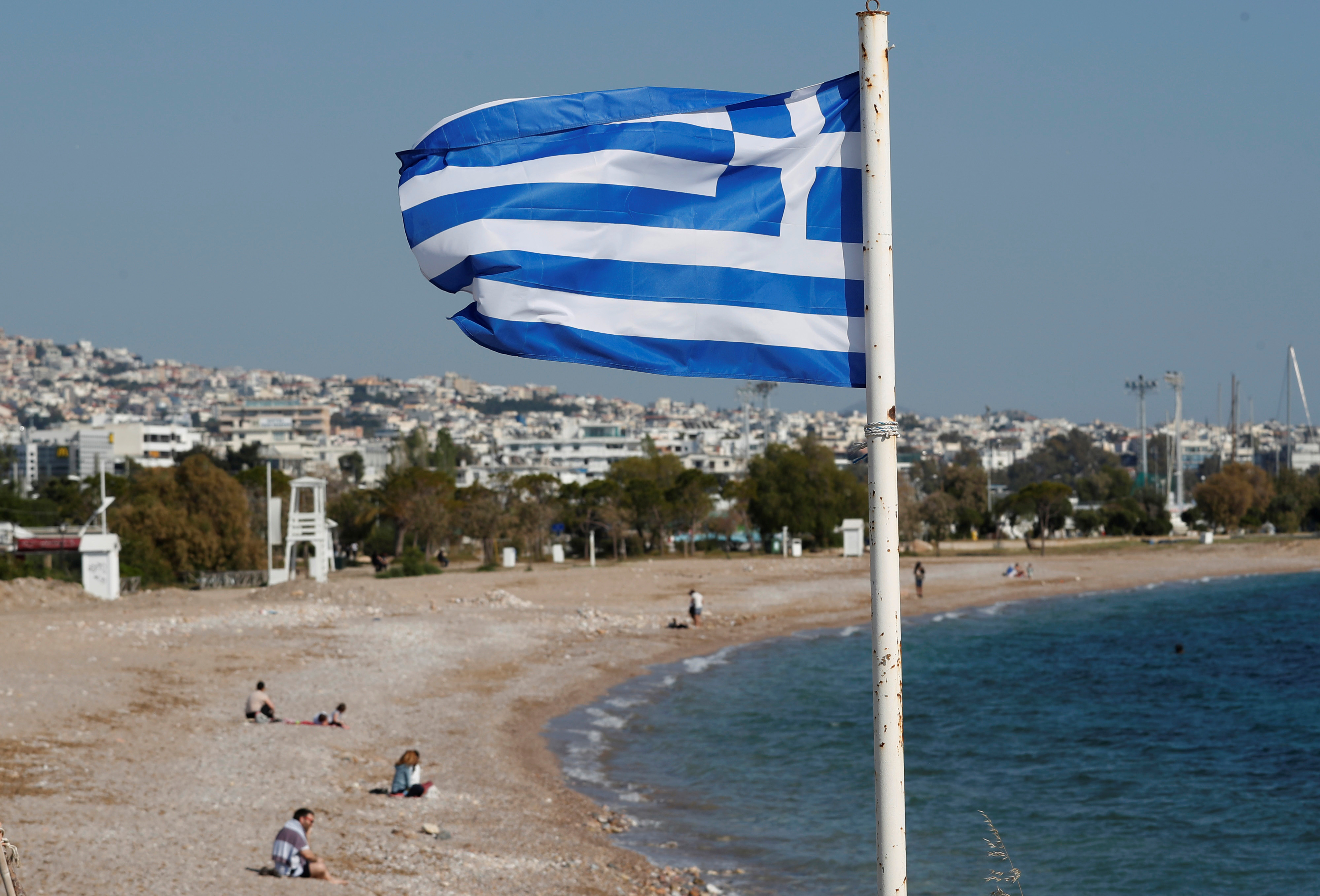 A Greek national flag flutters as people visit a beach, following the coronavirus disease (COVID-19) outbreak, in Athens, Greece, April 28, 2020. Picture taken April 28, 2020. REUTERS/Goran Tomasevic
