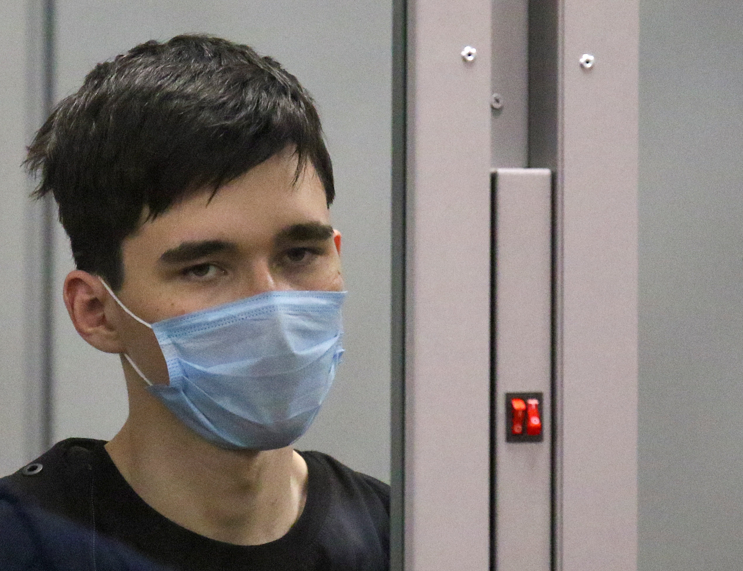 Ilnaz Galyaviev, a suspect in deadly school shooting at School Number 175, looks out of a defendants' cage during a court hearing in Kazan, Russia May 12, 2021. REUTERS/Artem Dergunov