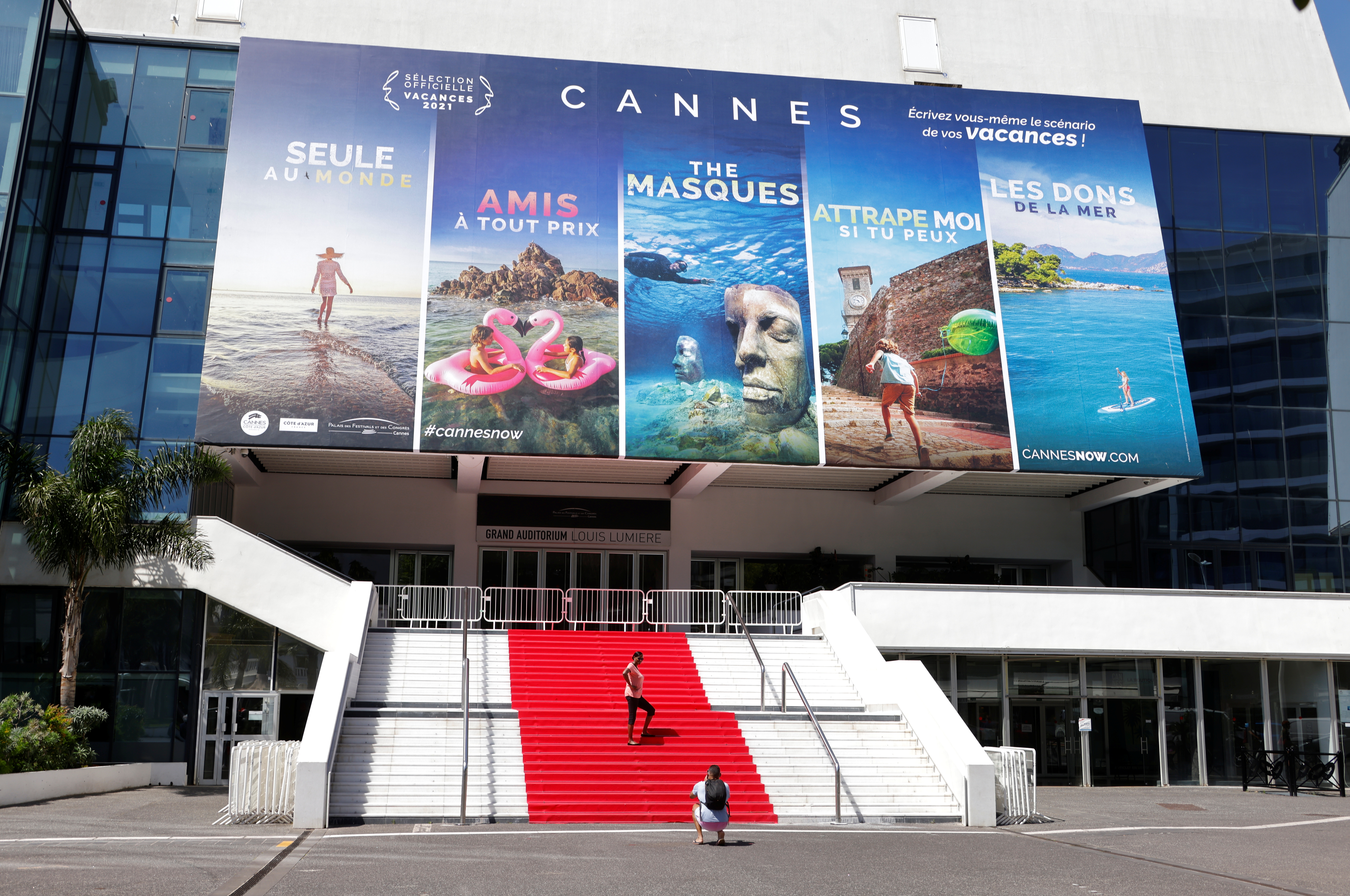 People stand on the red carpet of the Festival palace in Cannes as the French Riviera prepares for the 2021 edition of the Cannes Film Festival which will take place next July, in France, June 3, 2021.  REUTERS/Eric Gaillard