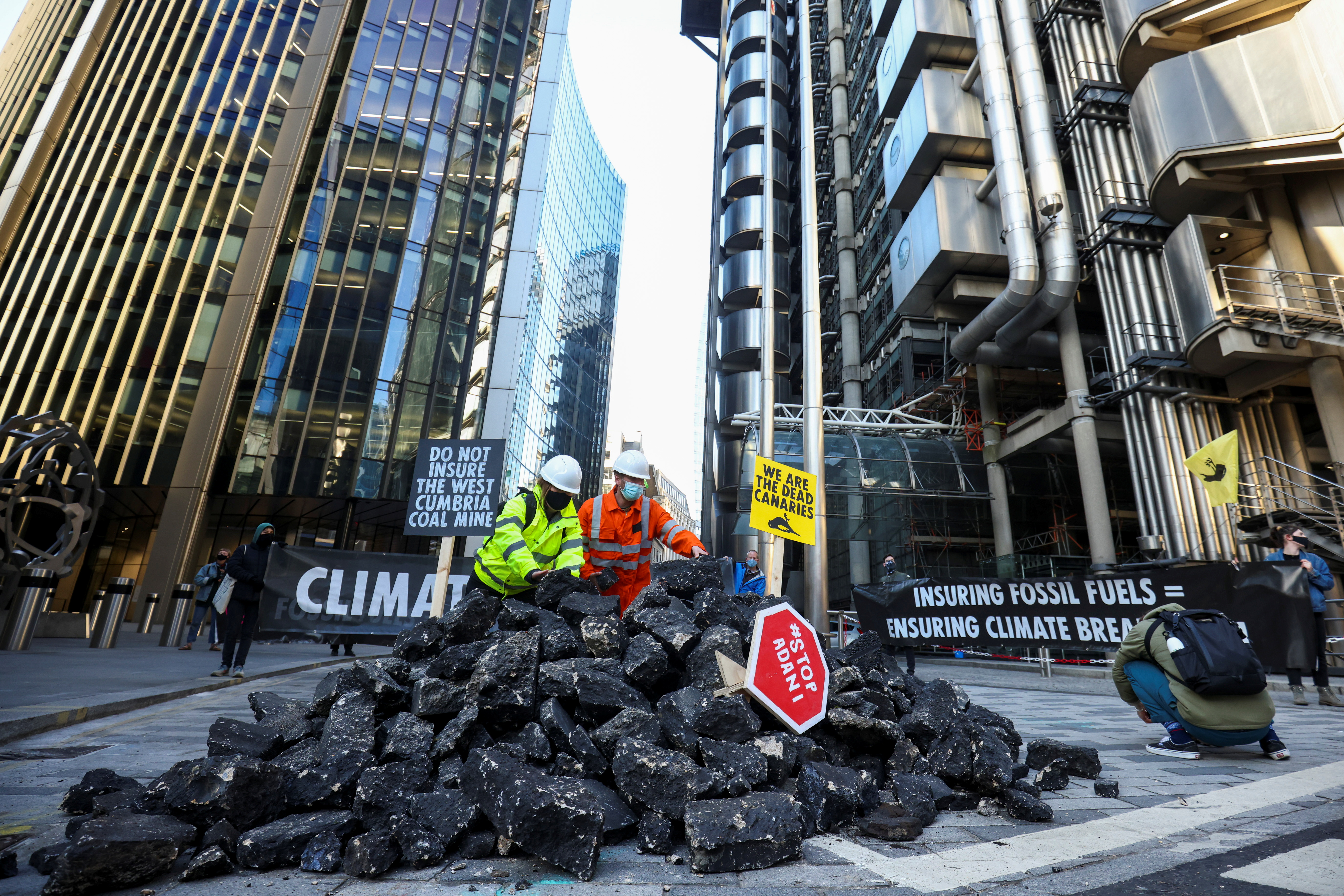 Activists from Extinction Rebellion, a global environmental movement, arrange fake coal, made from rocks, in the street during a protest outside the Lloyd's building in London, Britain April 23, 2021. REUTERS/Henry Nicholls - RC2K1N9L3E3I