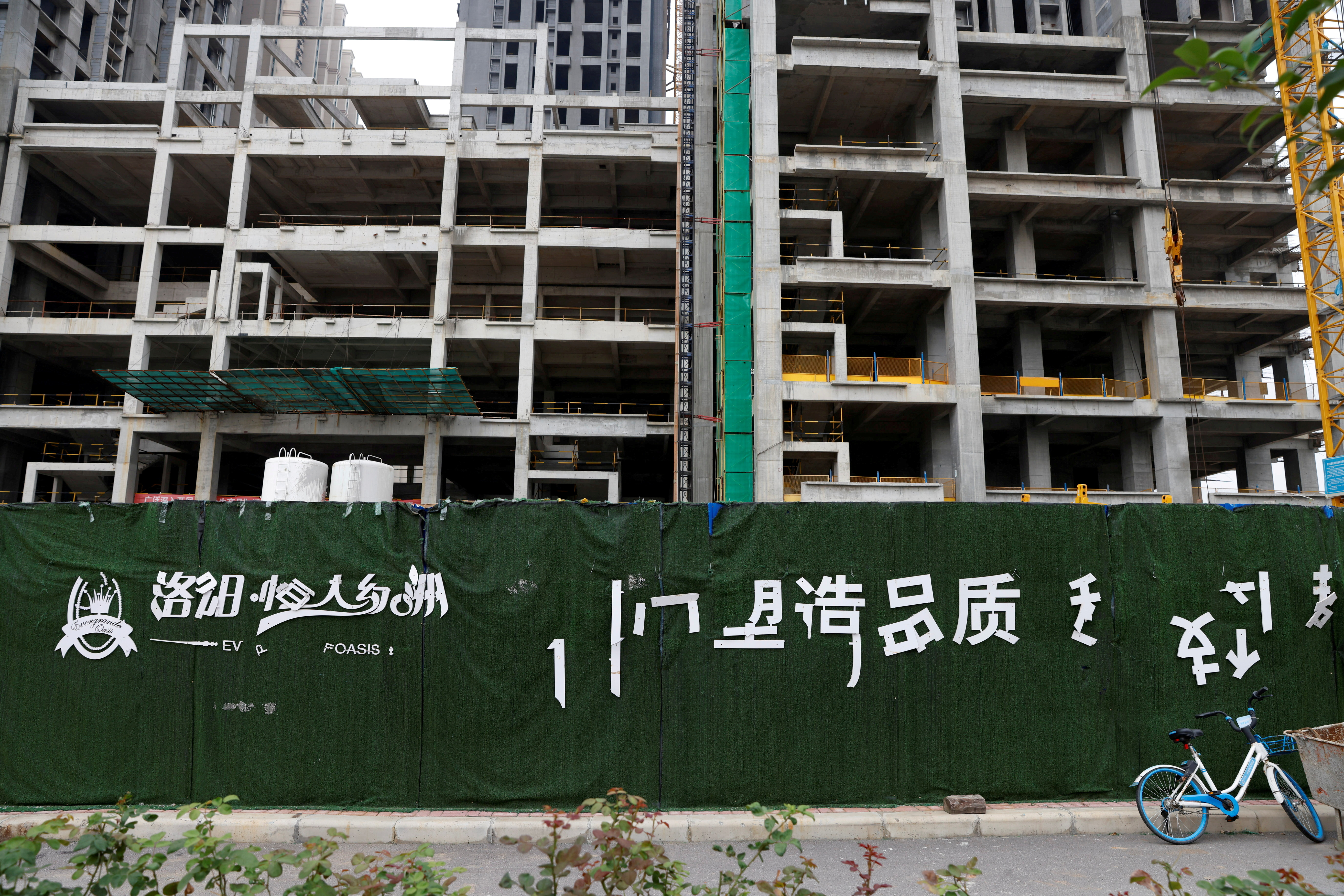 A peeling logo of the Evergrande Oasis, a housing complex developed by Evergrande Group, is seen outside the construction site where the residential buildings stand unfinished, in Luoyang, China September 16, 2021. Picture taken September 16, 2021. REUTERS/Carlos Garcia Rawlins/File Photo
