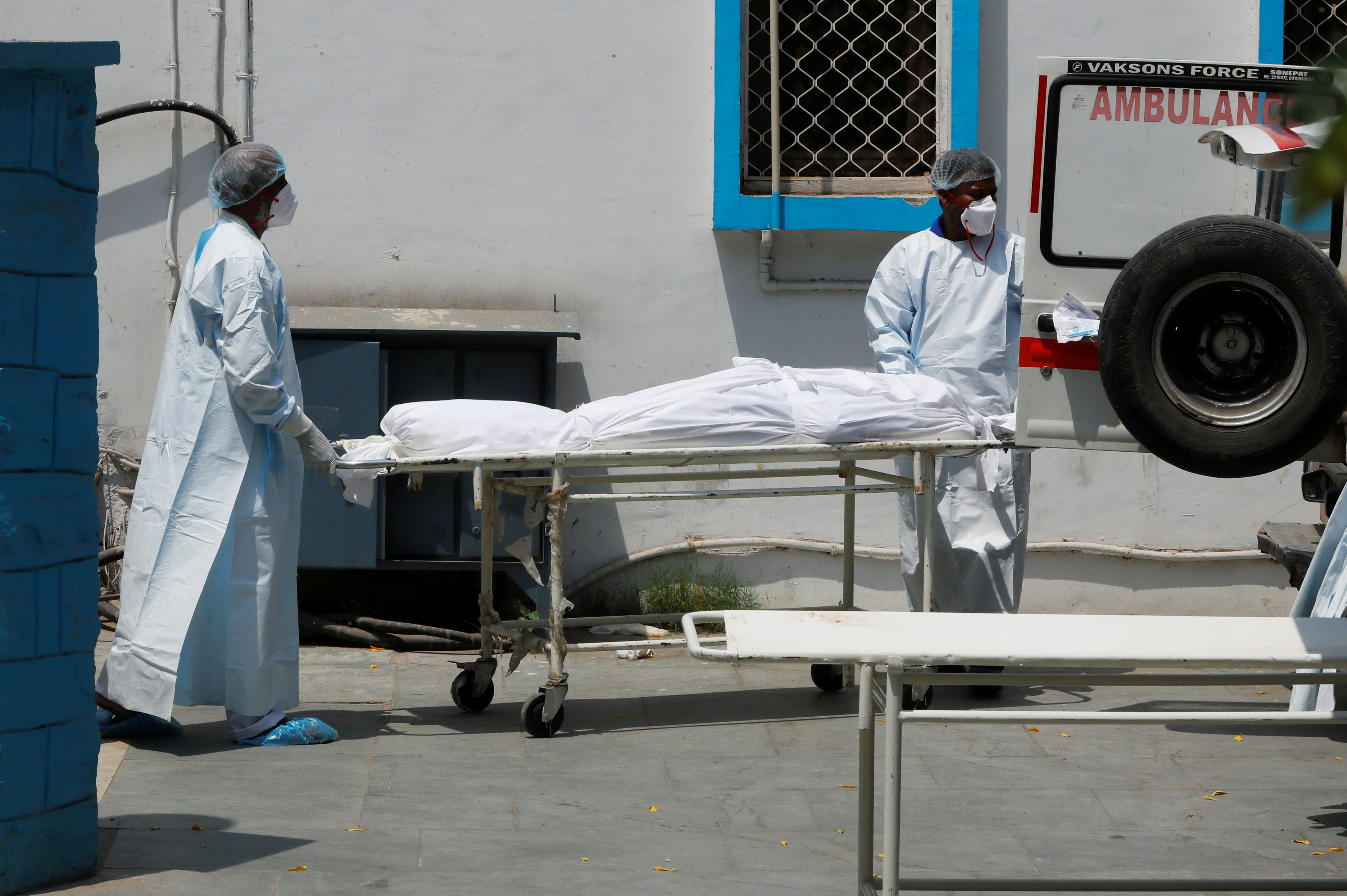 Mortuary workers load the body of a person, who died from the coronavirus disease (COVID-19), to an ambulance for cremation, at a hospital in New Delhi, India May 5, 2021. REUTERS/Adnan Abidi