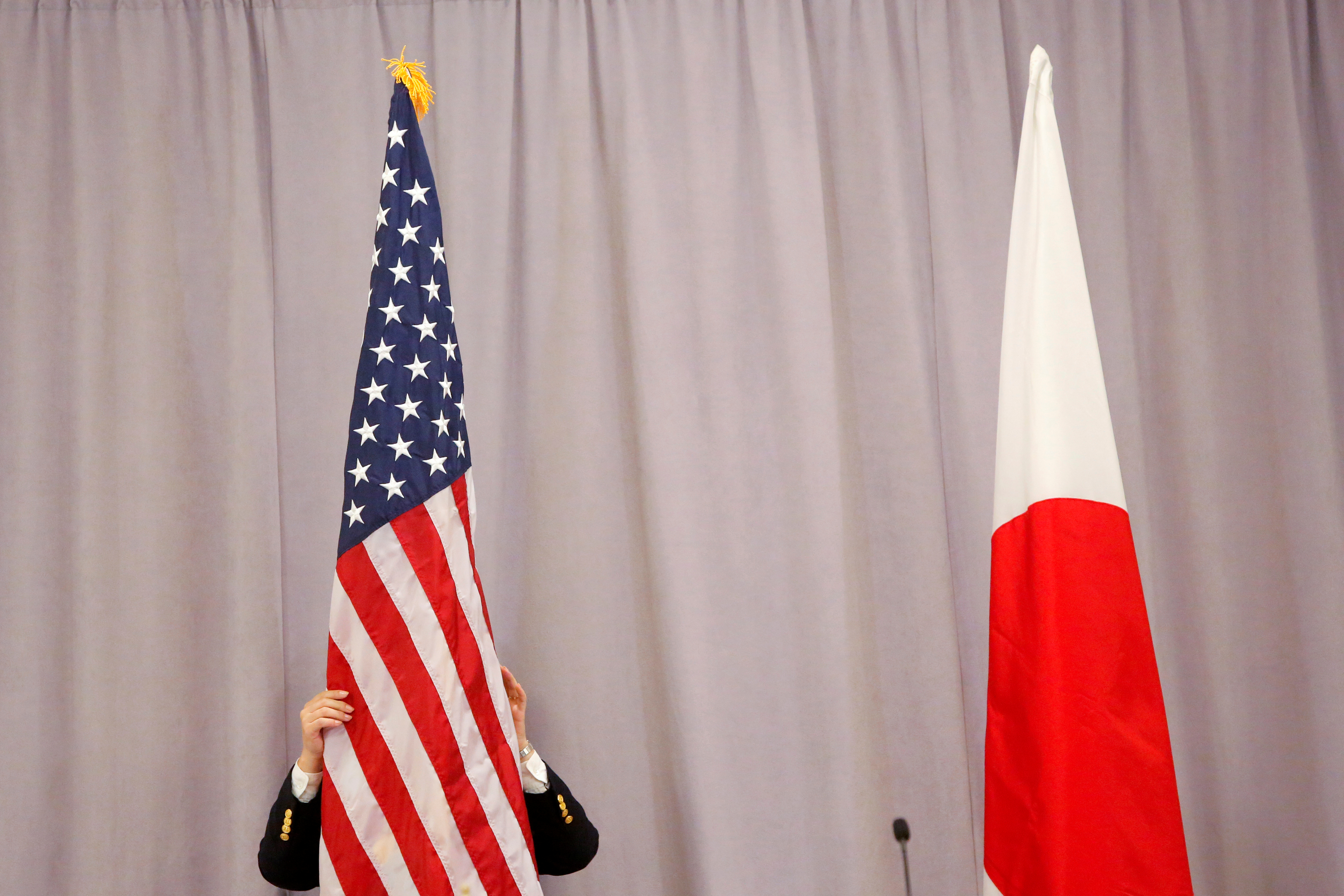 A worker adjusts the U.S. flag before Japanese Prime Minister Shinzo Abe addresses media following a meeting with President-elect Donald Trump in Manhattan, New York, U.S., November 17, 2016.  REUTERS/Andrew Kelly