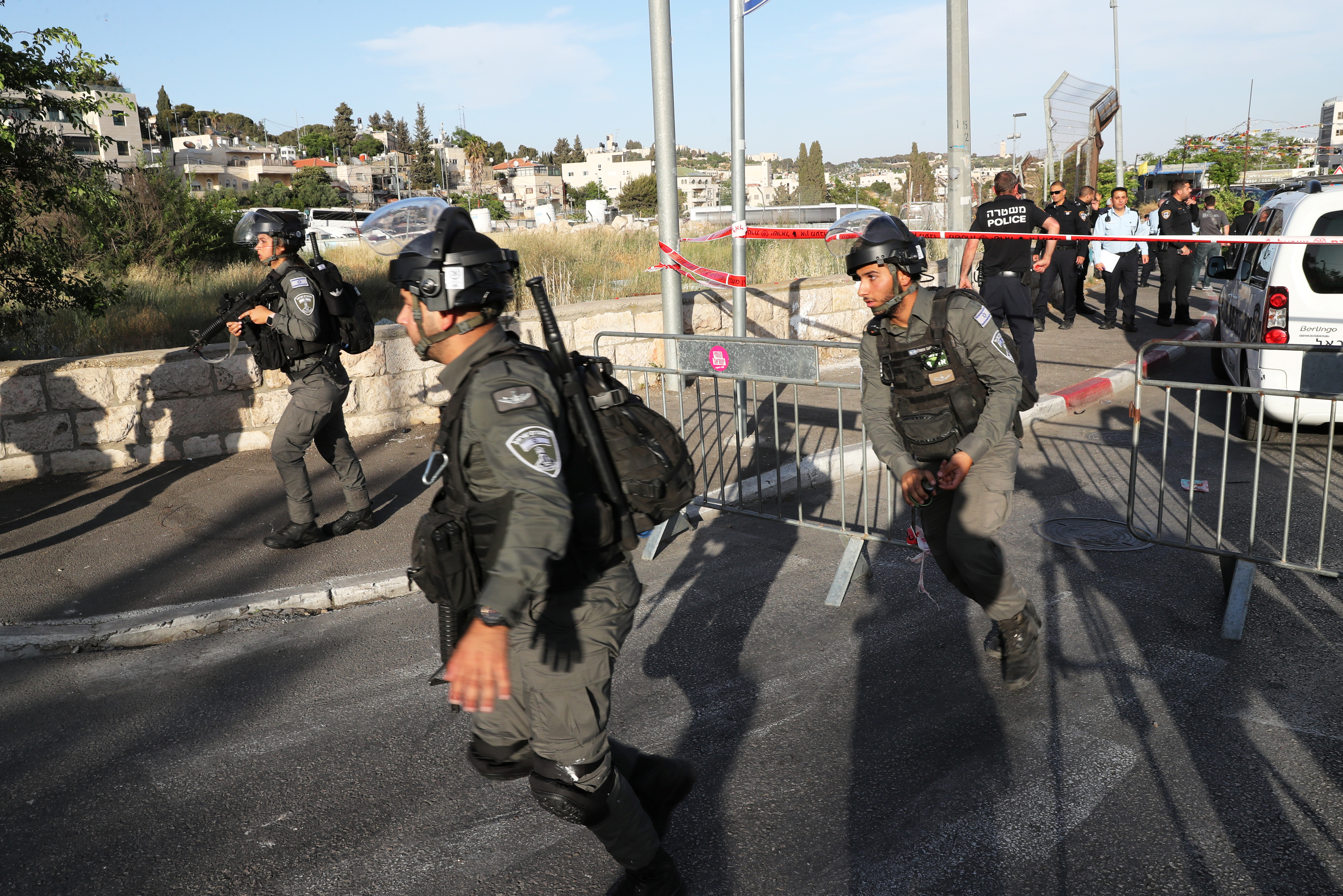 Israeli security forces run at the scene of what police said was a suspected car-ramming attack, at the entrance to Sheikh Jarrah neighbourhood of East Jerusalem May 16, 2021. REUTERS/Ronen Zvulun