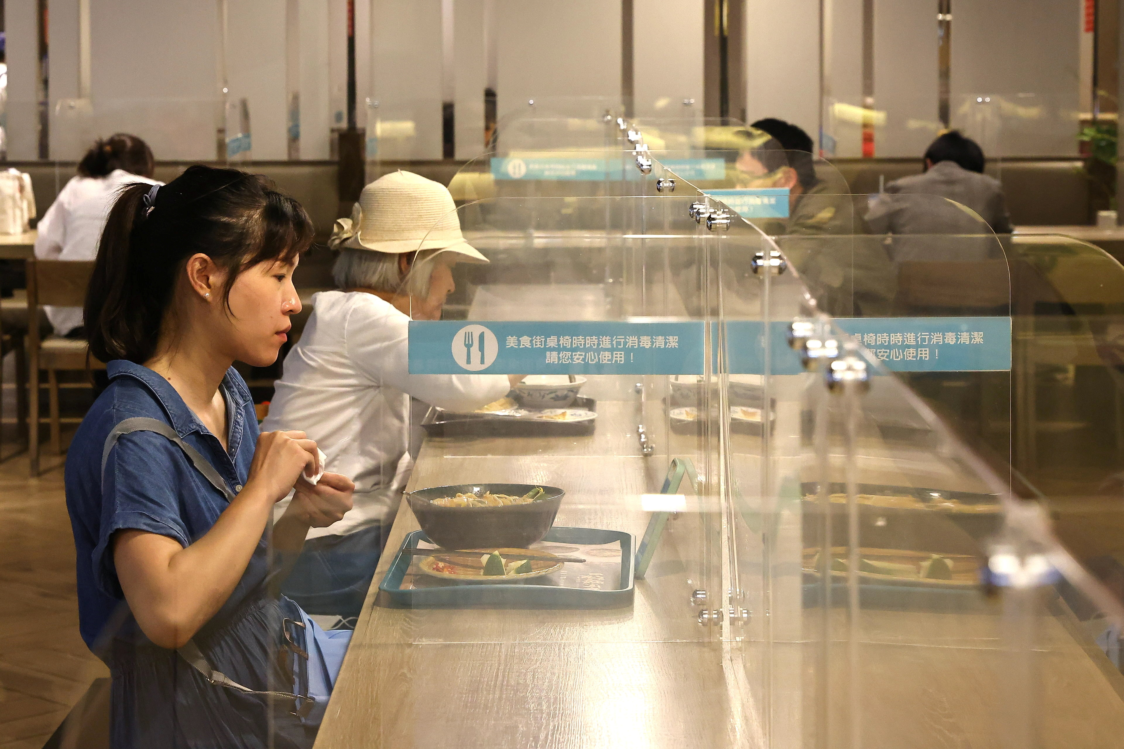People eat lunch between plastic partitions following the outbreak of coronavirus disease (COVID-19), in Taipei, Taiwan, May 12, 2021. REUTERS/Ann Wang