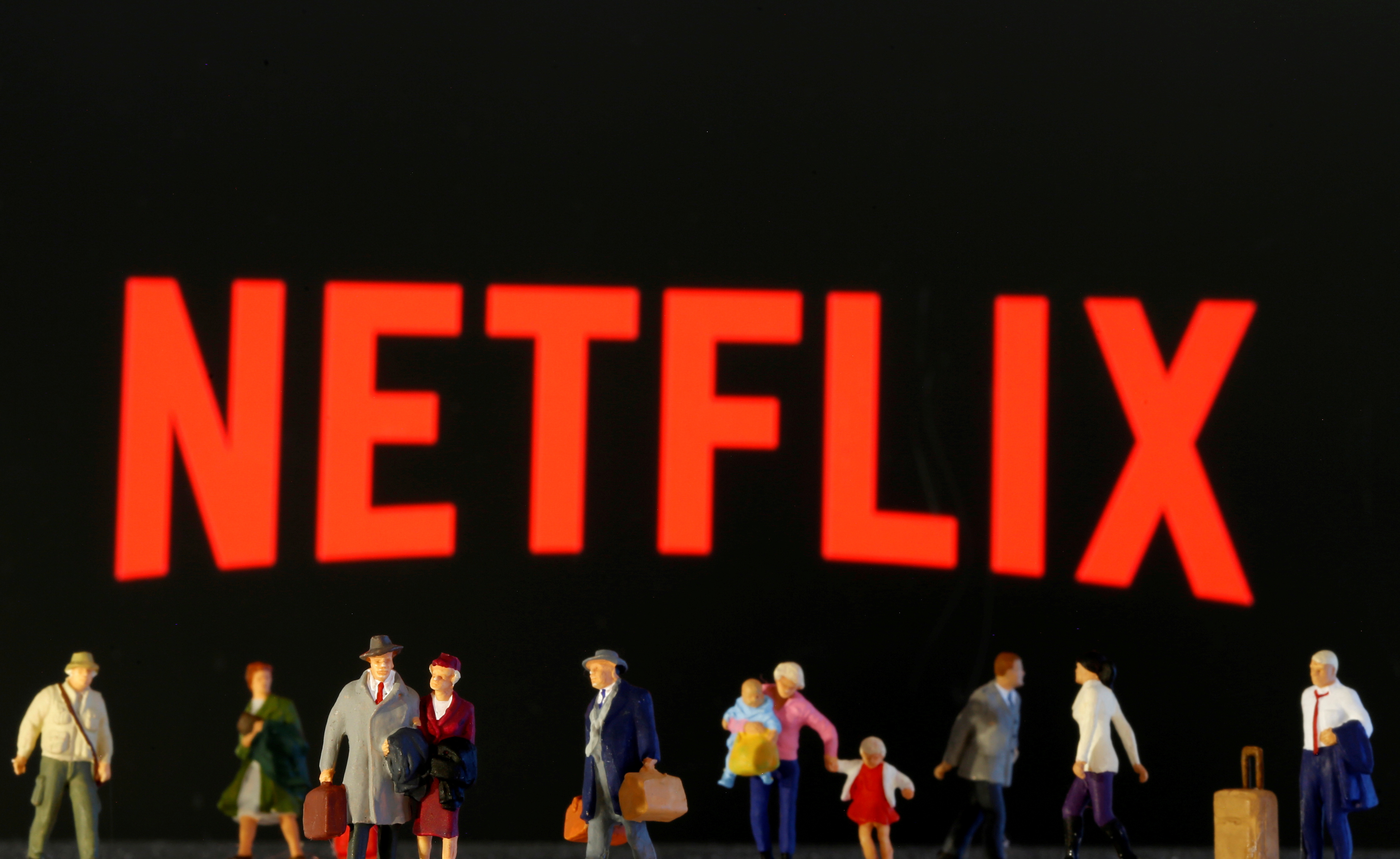 Small toy figures are seen in front of diplayed Netflix logo in this illustration taken March 19, 2020. REUTERS/Dado Ruvic/Illustration/File Photo
