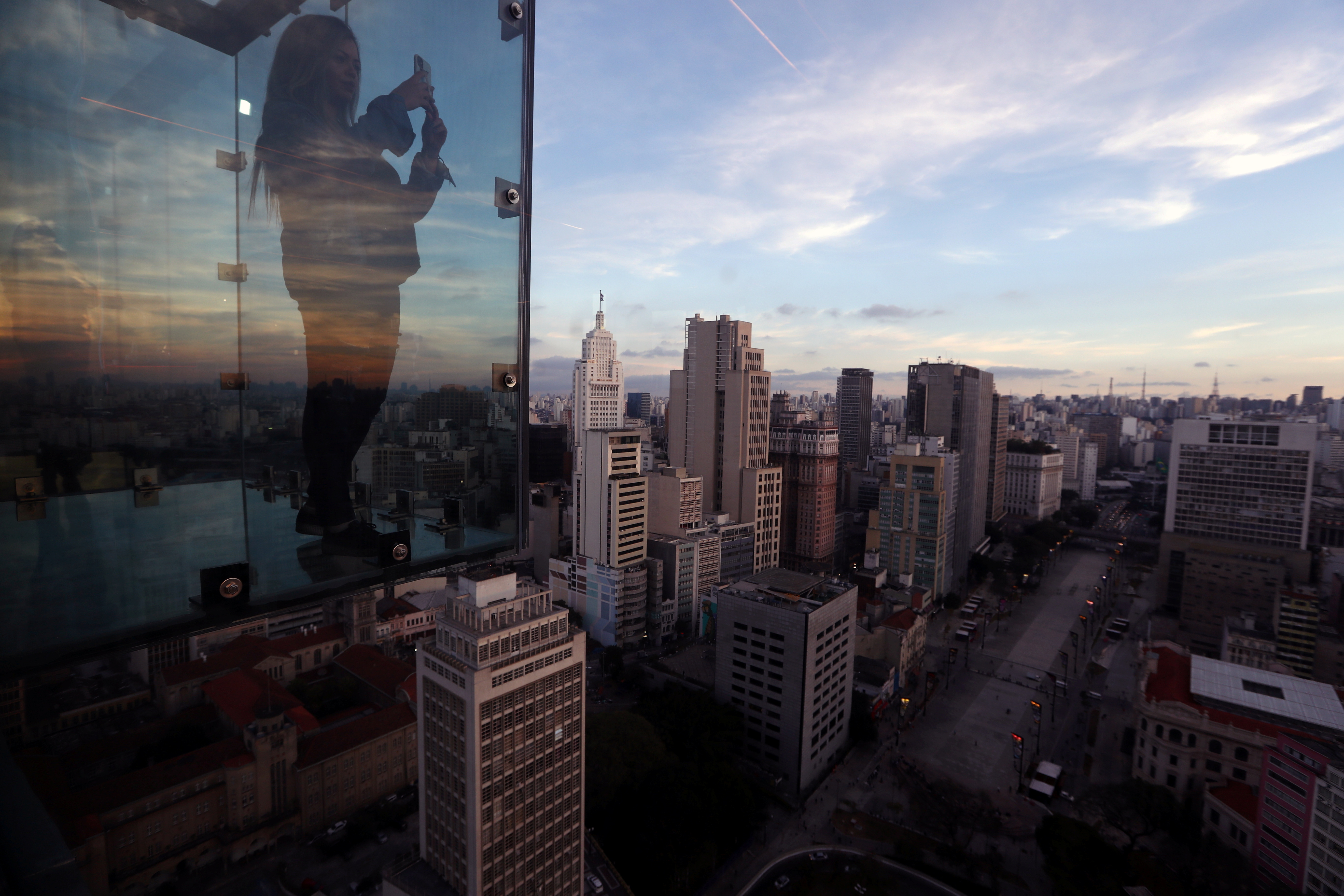 Influencer Julia Paiva takes a picture inside Sampa Sky, a reinforced glass box that protrudes beyond the building and allows to see not only the horizon, but also the ground below your feet, in downtown Sao Paulo, Brazil, August 3, 2021. REUTERS/Amanda Perobelli
