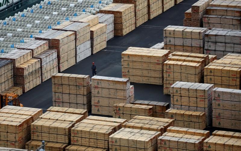 A worker walks among processed timber at a port in Keihin industrial zone in Kawasaki, Japan, September 14, 2016. Picture taken September 14, 2016. REUTERS/Toru Hanai/File Photo