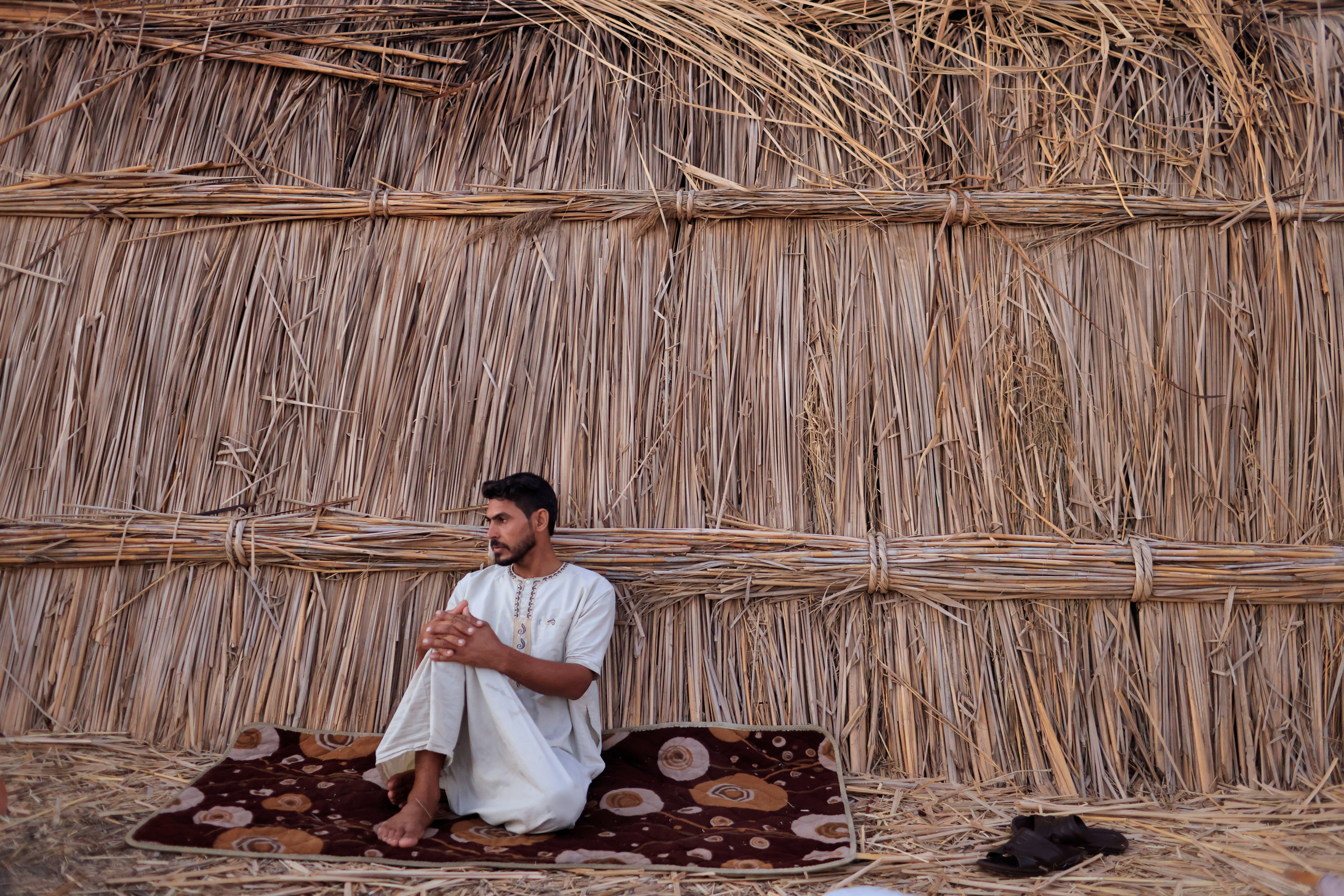 Sabah Thamer al-Baher sits at his home in the Chebayesh marsh, Dhi Qar province, Iraq, August 15, 2021. Iraq's 2020-2021 rainfall season was the second driest in 40 years, according to the United Nations, causing the salinity of the wetlands to rise to dangerous levels. Animals fell sick and died, and Baher was forced to buy fresh drinking water for his own herd of around 20 buffaloes, his only source of income. Another drought is predicted for 2023 as climate change, pollution and upstream damming keep Iraq trapped in a cycle of recurring water crises.