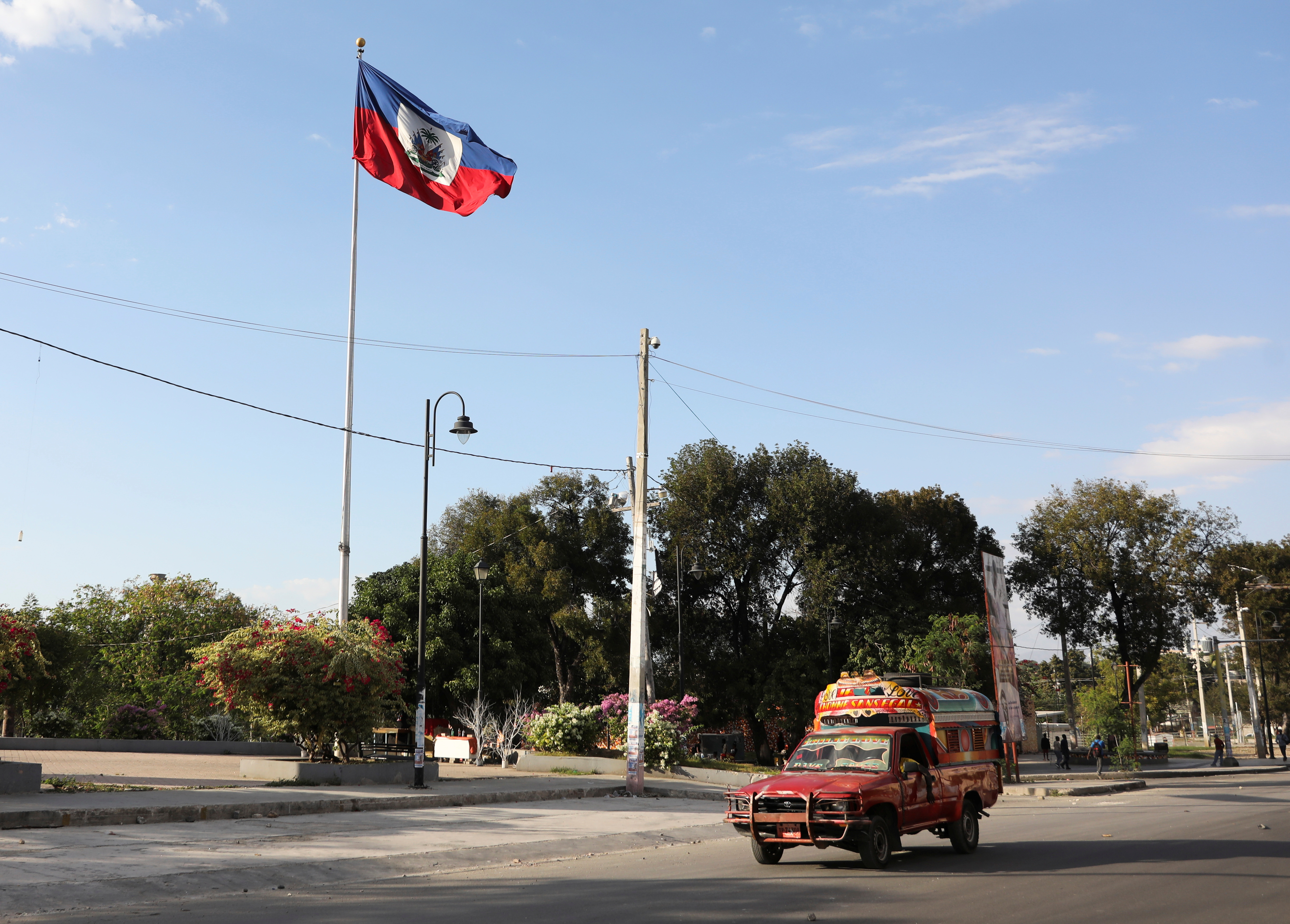 A Tap-Tap (a collective transportation vehicle) drives past Haiti's national flag, in Port-au-Prince, Haiti February 9, 2021. REUTERS/Valerie Baeriswyl