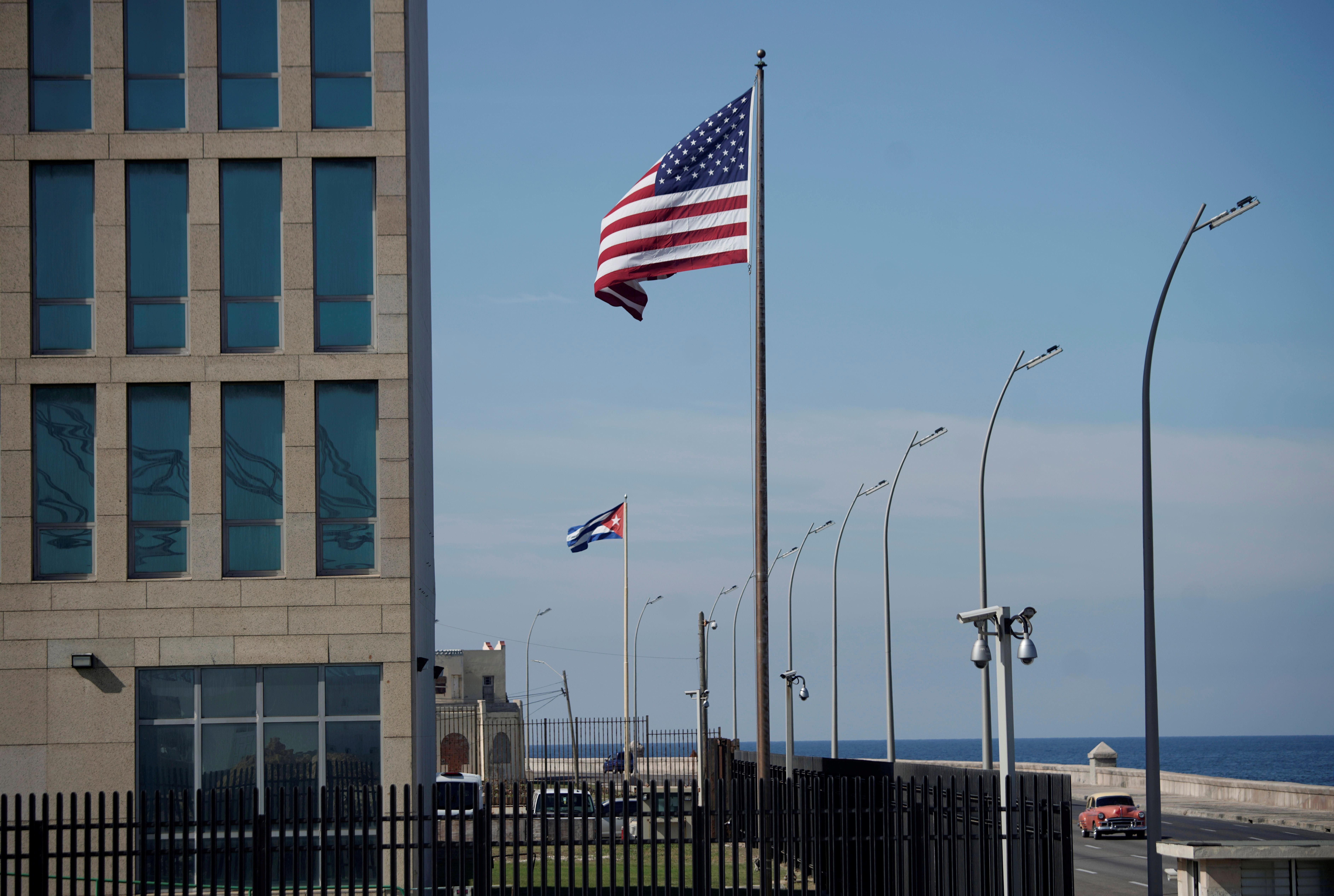 A view of Cuban and U.S. flags beside the U.S. Embassy in Havana, Cuba, December 15, 2020. REUTERS/Alexandre Meneghini/File Photo