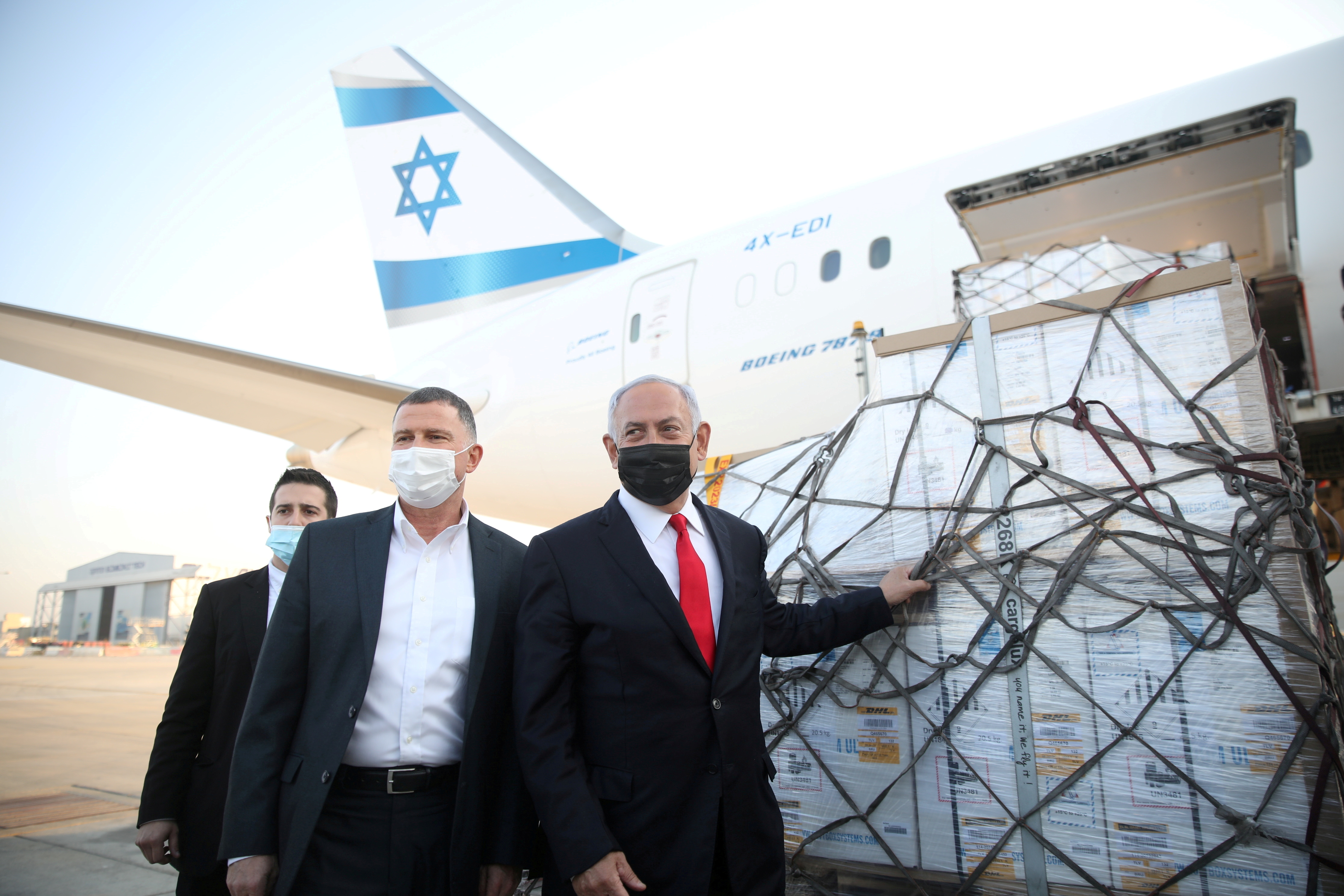 Israel Prime Minister Benjamin Netanyahu and Health Minister Yuli Edelstein attend the arrival of a plane with a shipment of Pfizer-BioNTech coronavirus disease (COVID-19) vaccines, at Ben Gurion airport, near the city of Lod, Israel, January 10, 2021. Motti Millrod/Pool via REUTERS
