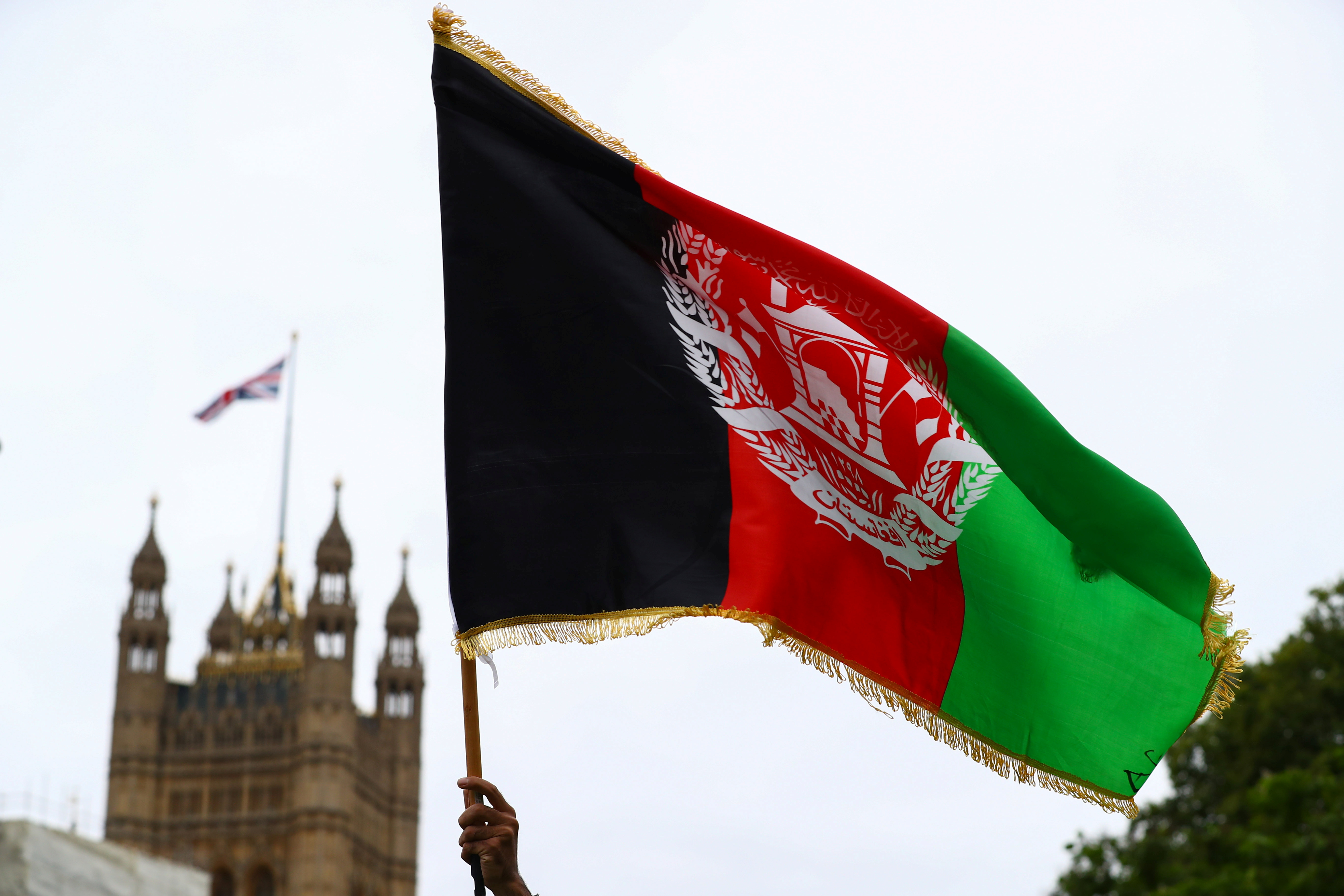 A demonstrator holds an Afghan flag during a
