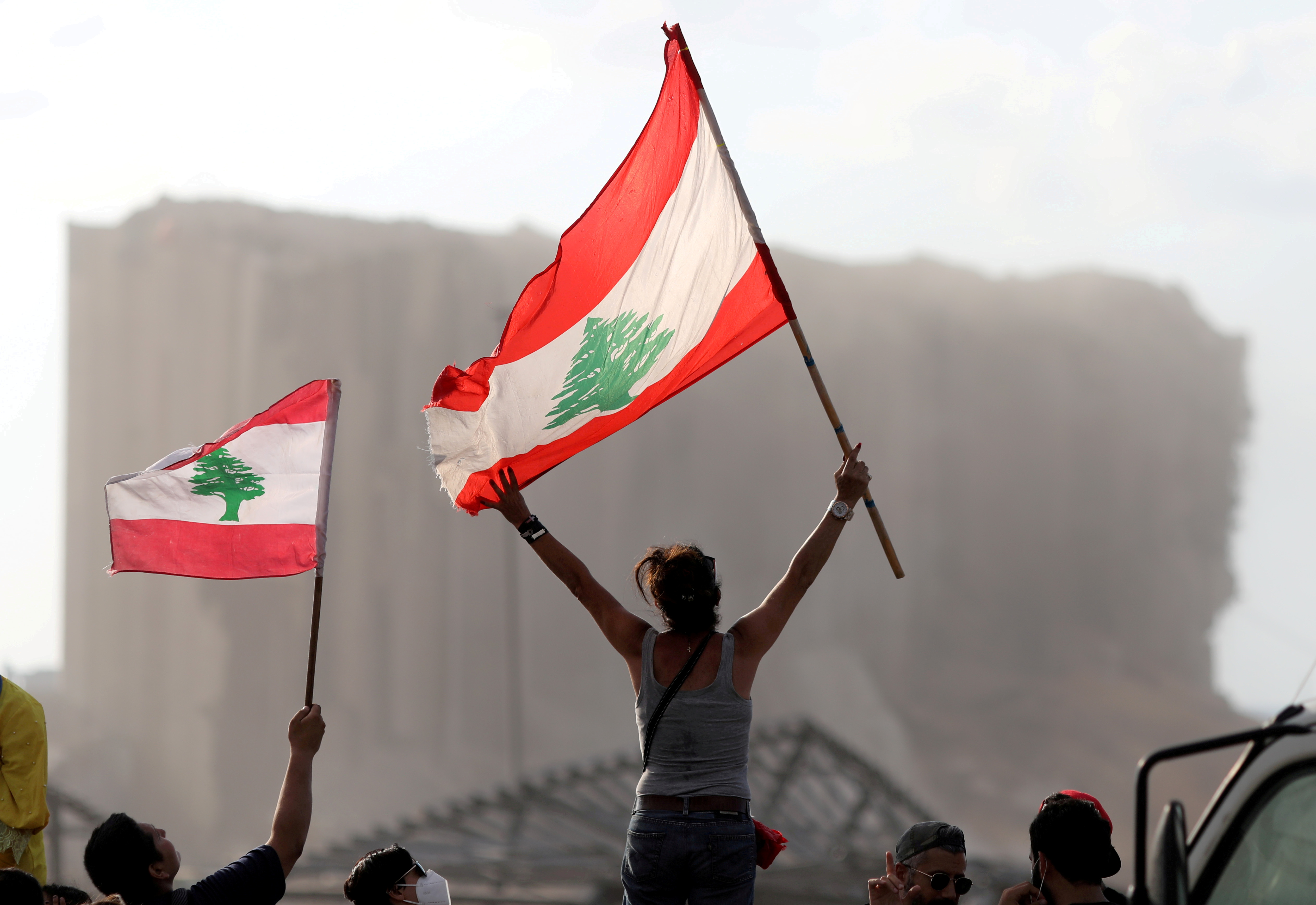 Demonstrators wave Lebanese flags during protests near the site of a blast at Beirut's port area, Lebanon August 11, 2020. REUTERS/Goran Tomasevic/File Photo
