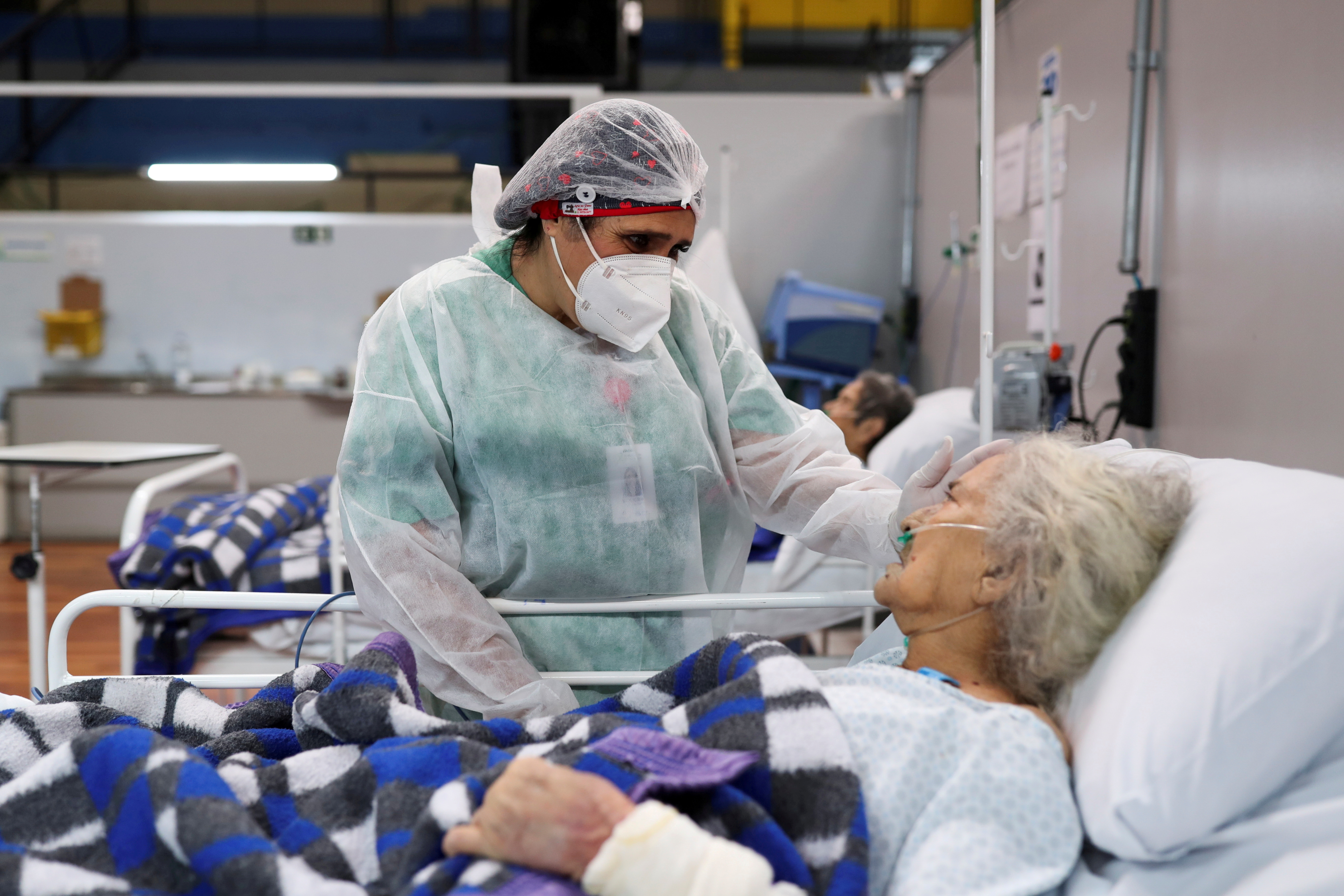 Nurse Walkiria Ribeiro speaks to Joana Maria Rodrigues, 80, as she works during the New Year at a field hospital set up at a sports gym to treat patients suffering with the coronavirus disease (COVID-19) in Santo Andre, Sao Paulo state, Brazil, January 1, 2021. REUTERS/Amanda Perobelli/File Photo