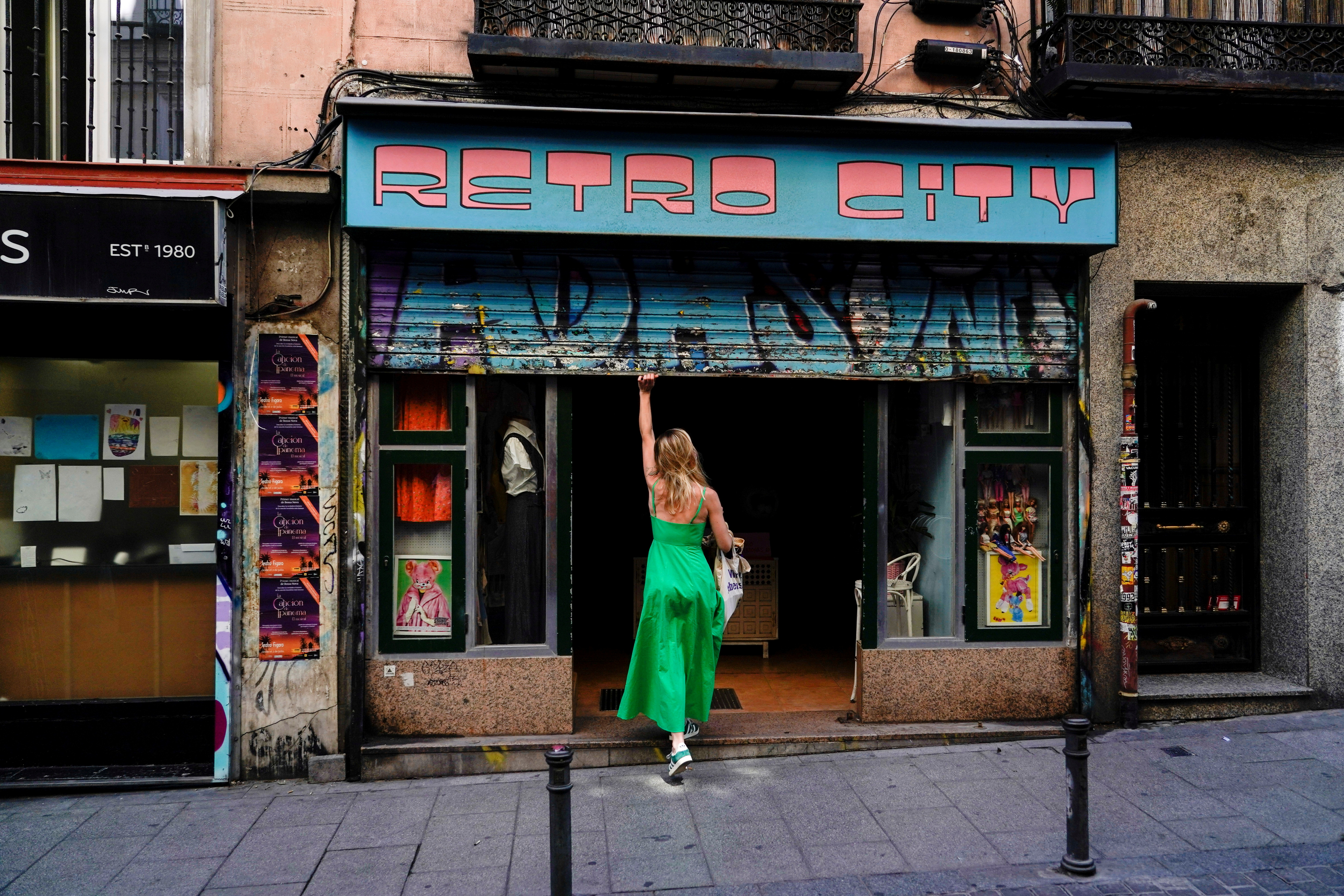 A woman opens a shop at a commercial district in Madrid, Spain, July 27, 2021. REUTERS/Juan Medina