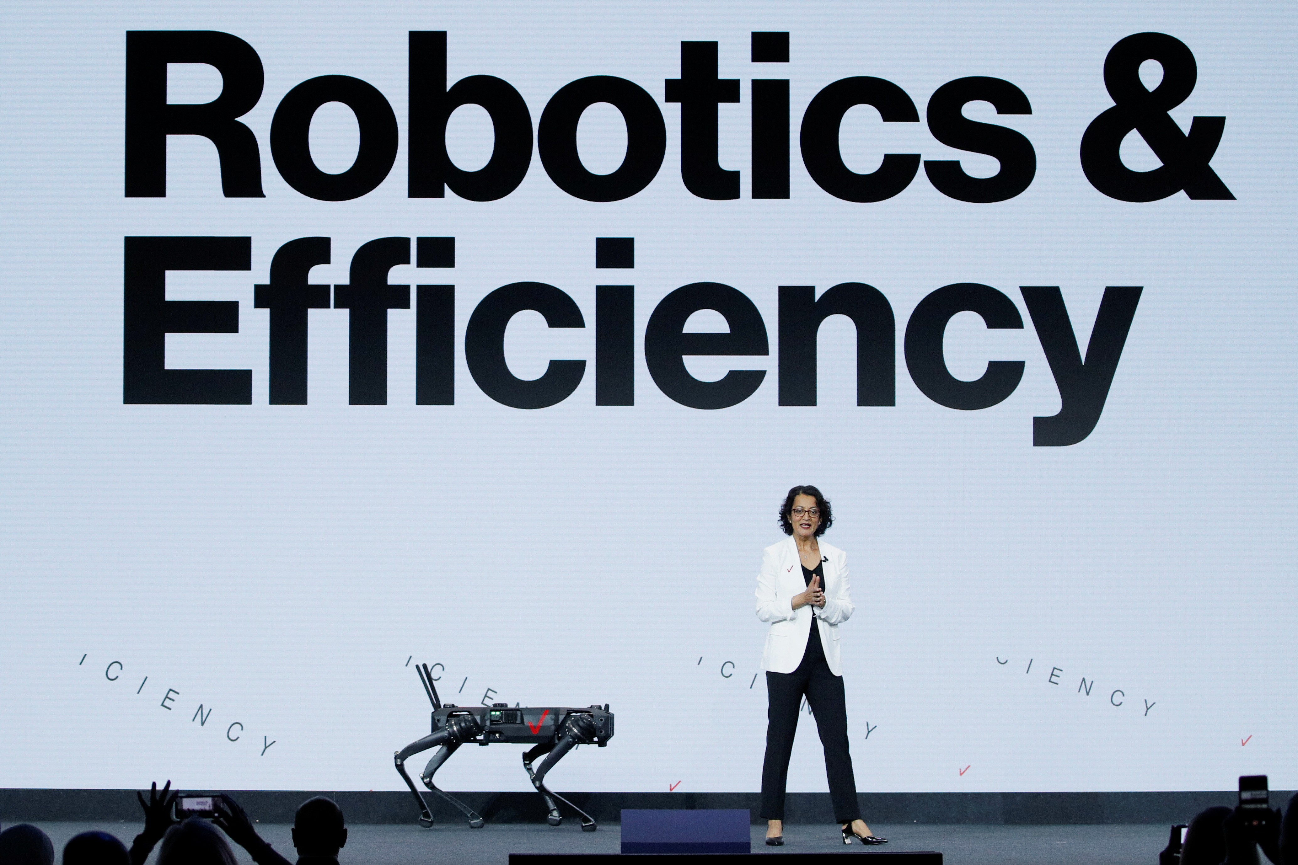 Rima Qureshi, EVP Chief Strategy Officer of Verizon, stands next to a robot, as she gives a speech during the Mobile World Congress (MWC) in Barcelona, Spain, June 28, 2021. REUTERS/Albert Gea