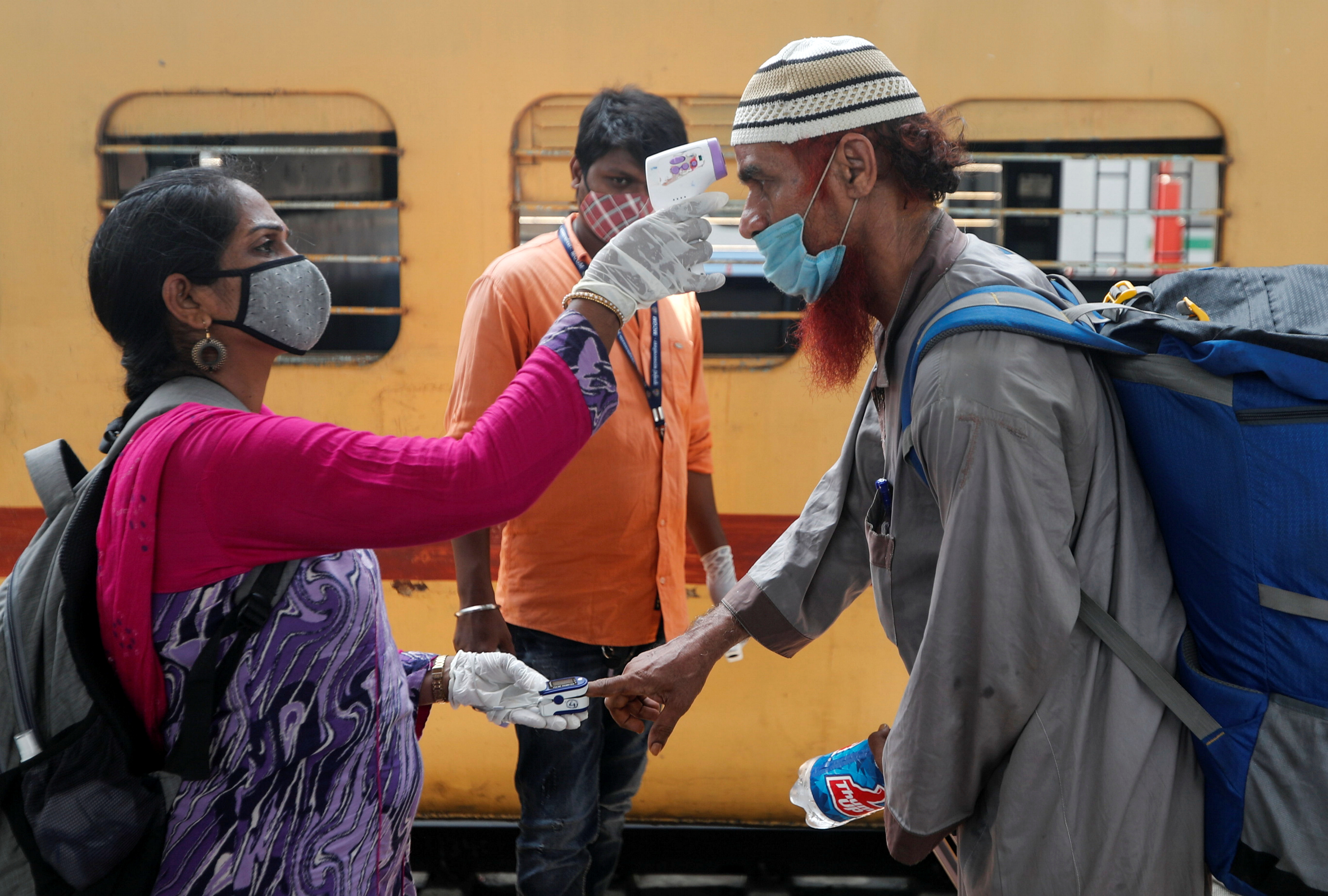 A health worker checks a passenger's temperature and pulse at a railway station platform amidst the spread of the coronavirus disease (COVID-19) in Mumbai, India, April 7, 2021. REUTERS/Francis Mascarenhas