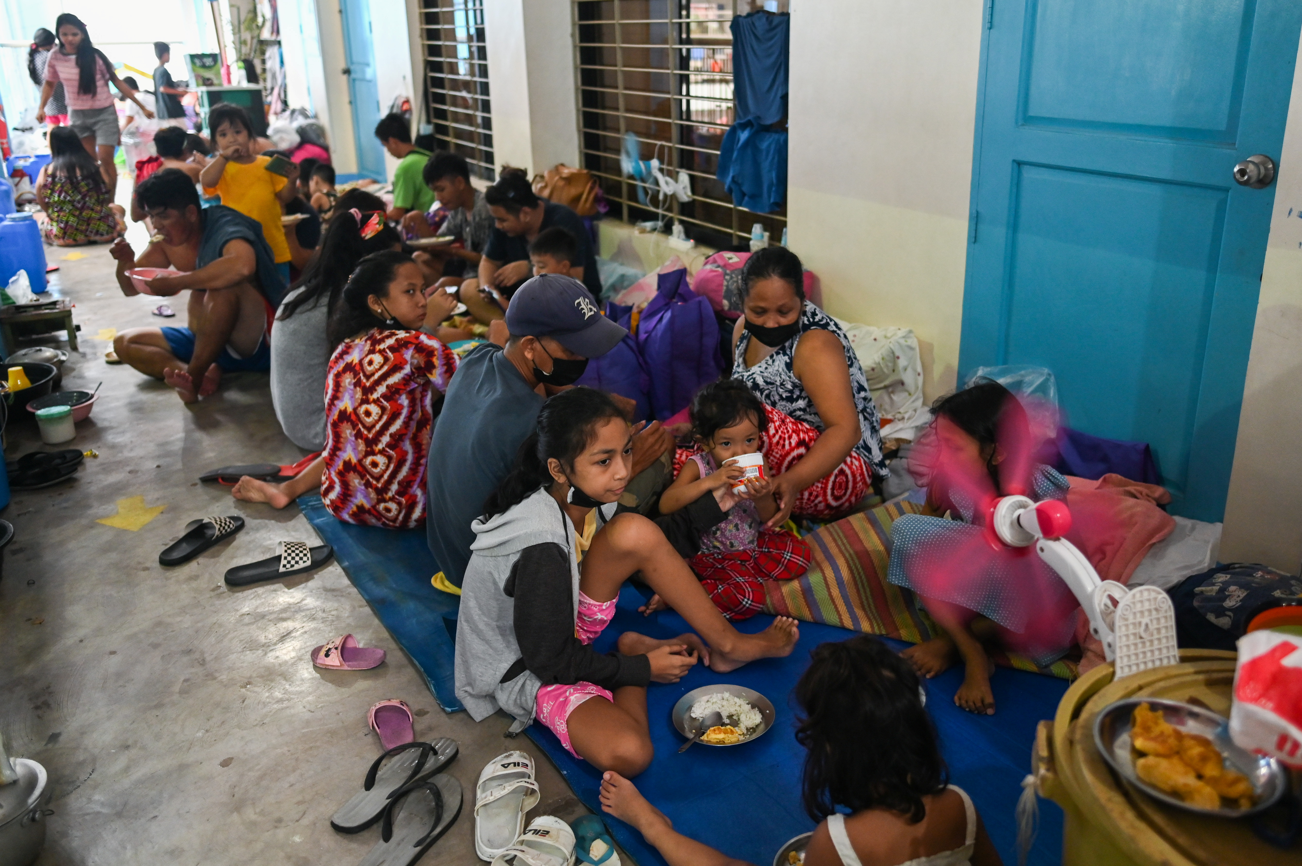 Residents have a meal after being evacuated at a school amid heavy rains that caused flooding in some areas in Marikina city, Metro Manila, Philippines, July 24, 2021. REUTERS/Lisa Marie David