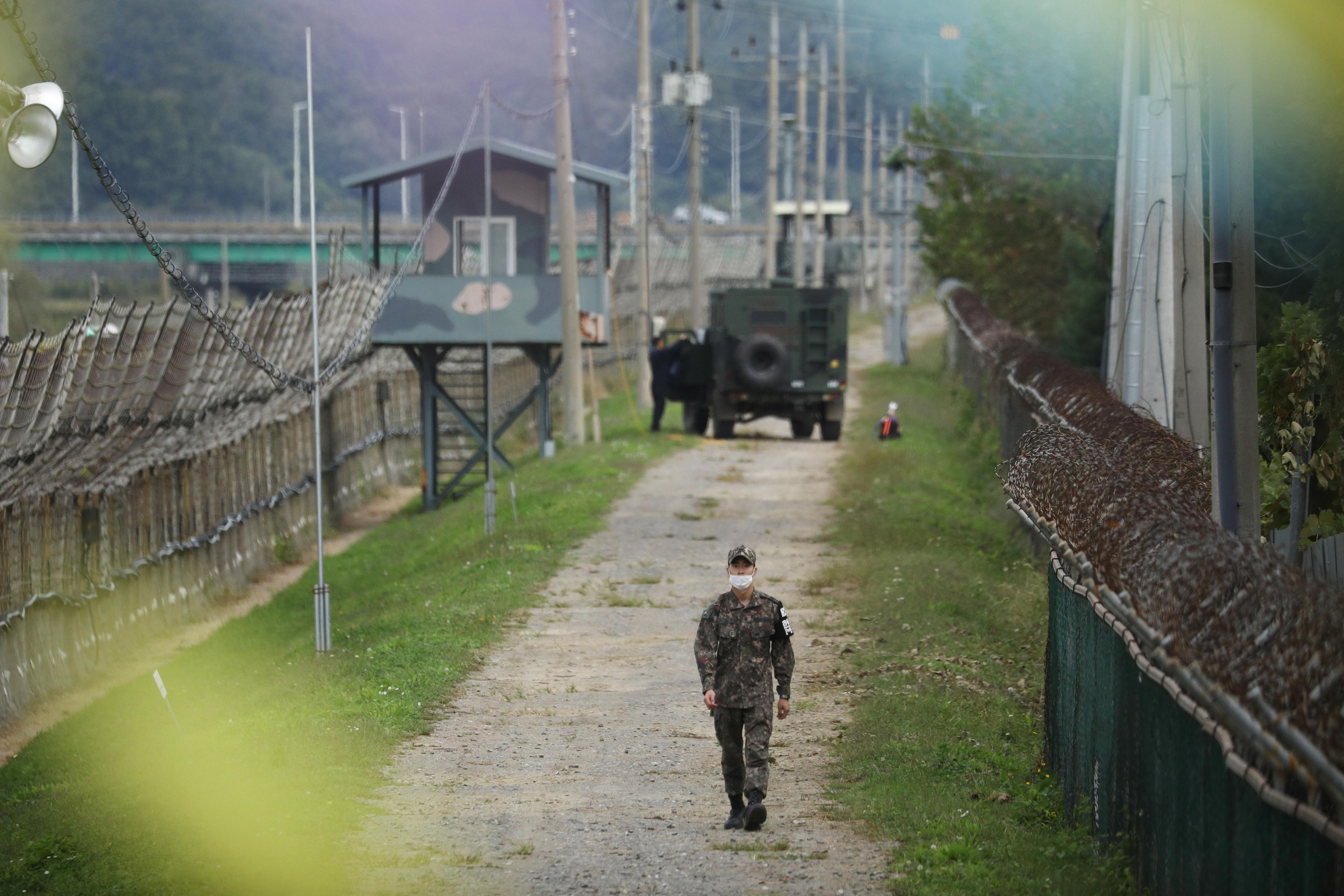 یک سرباز کره جنوبی در امتداد یک حصار نظامی در نزدیکی منطقه غیرنظامی جدا کننده دو کره در پاجو ، کره جنوبی ، 28 سپتامبر 2021 قدم می زند. رویترز/کیم هنگ جی
