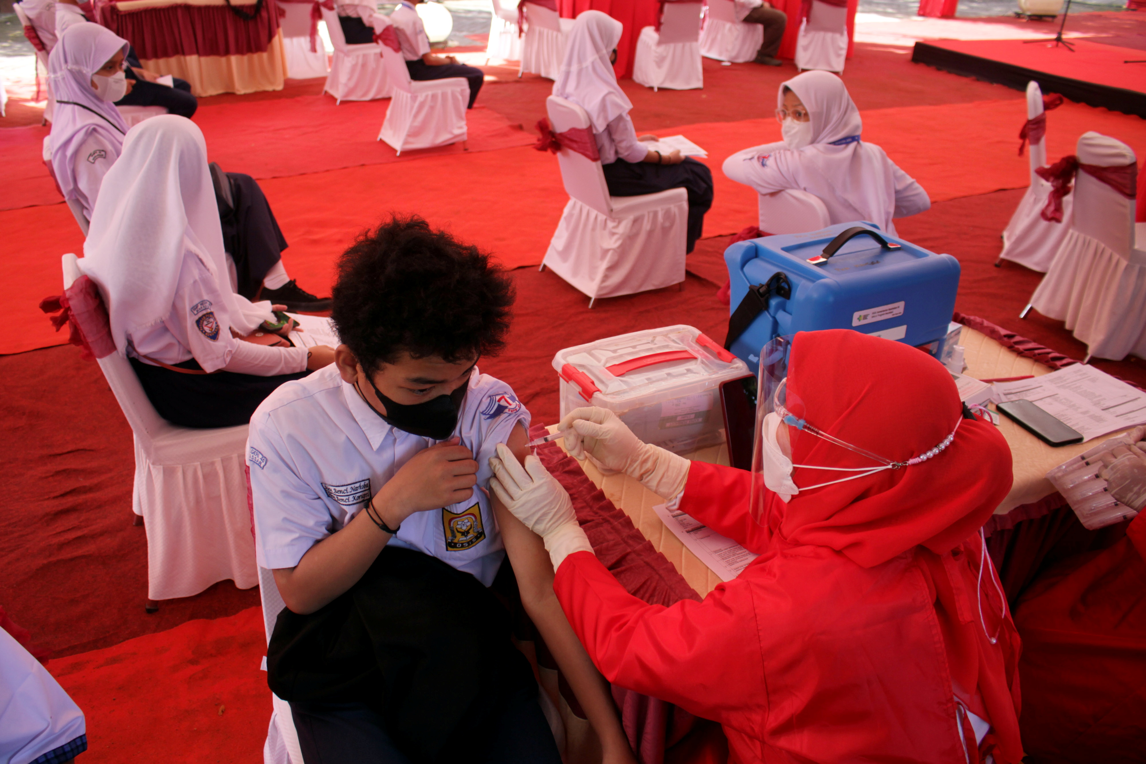 A student receives a coronavirus disease (COVID-19) vaccine during a massive student vaccination program amid a sharp rise in COVID-19 cases in Makassar, South Sulawesi province, Indonesia, July 14, 2021.  Antara Foto / Arnas Padda / via REUTERS