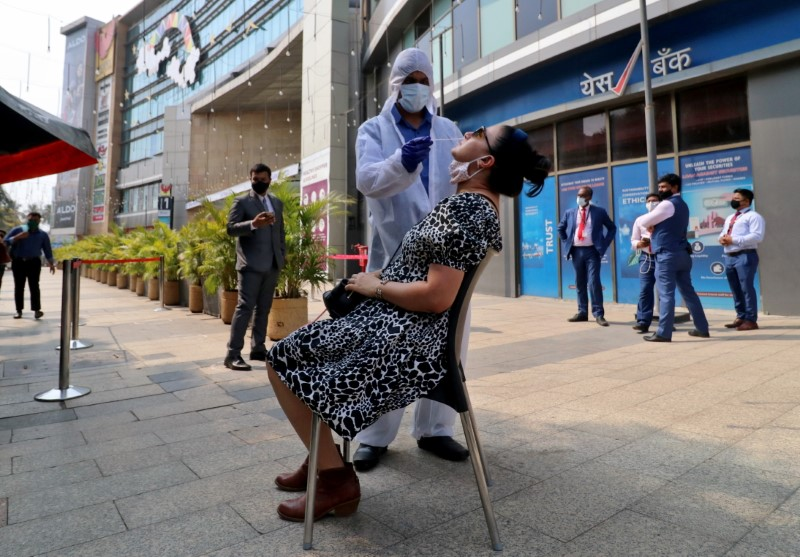 A healthcare worker collects a swab sample from a woman during a rapid antigen testing campaign for coronavirus disease (COVID-19), outside a shopping mall in Mumbai, India, March 22, 2021. REUTERS/Niharika Kulkarni