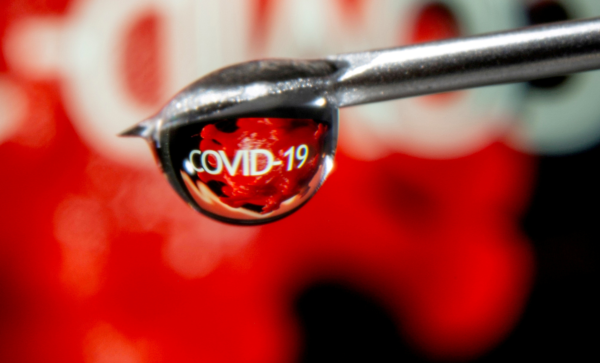 """The word """"COVID-19"""" is reflected in a drop on a syringe needle in this illustration taken November 9, 2020. REUTERS/Dado Ruvic/Illustration/File Photo"""