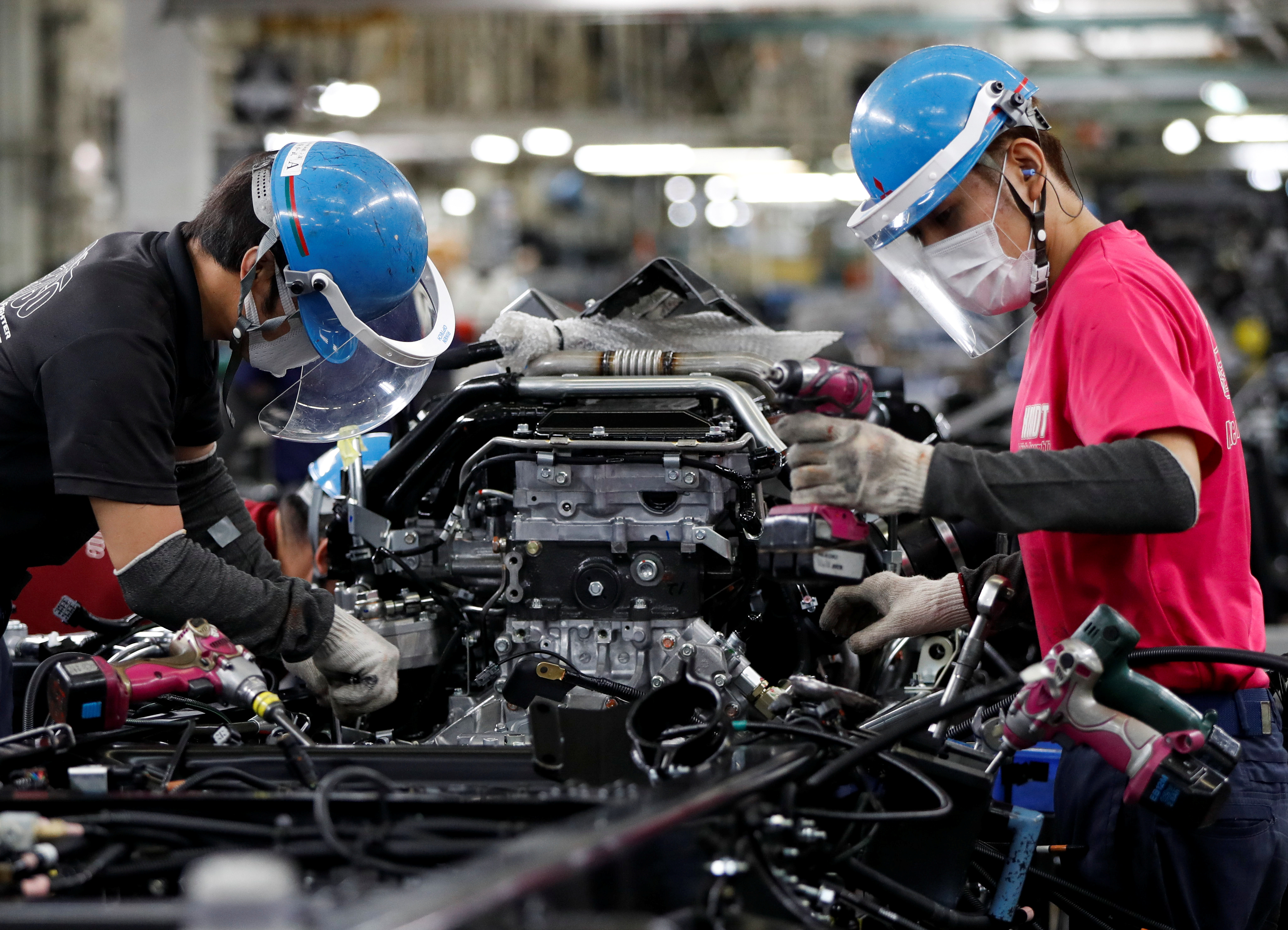 Employees wearing protective face masks and face guards work on the automobile assembly line, during the outbreak of the coronavirus disease (COVID-19), at Kawasaki factory of Mitsubishi Fuso Truck and Bus Corp., owned by Germany-based Daimler AG, in Kawasaki, south of Tokyo, Japan May 18, 2020.  REUTERS/Issei Kato