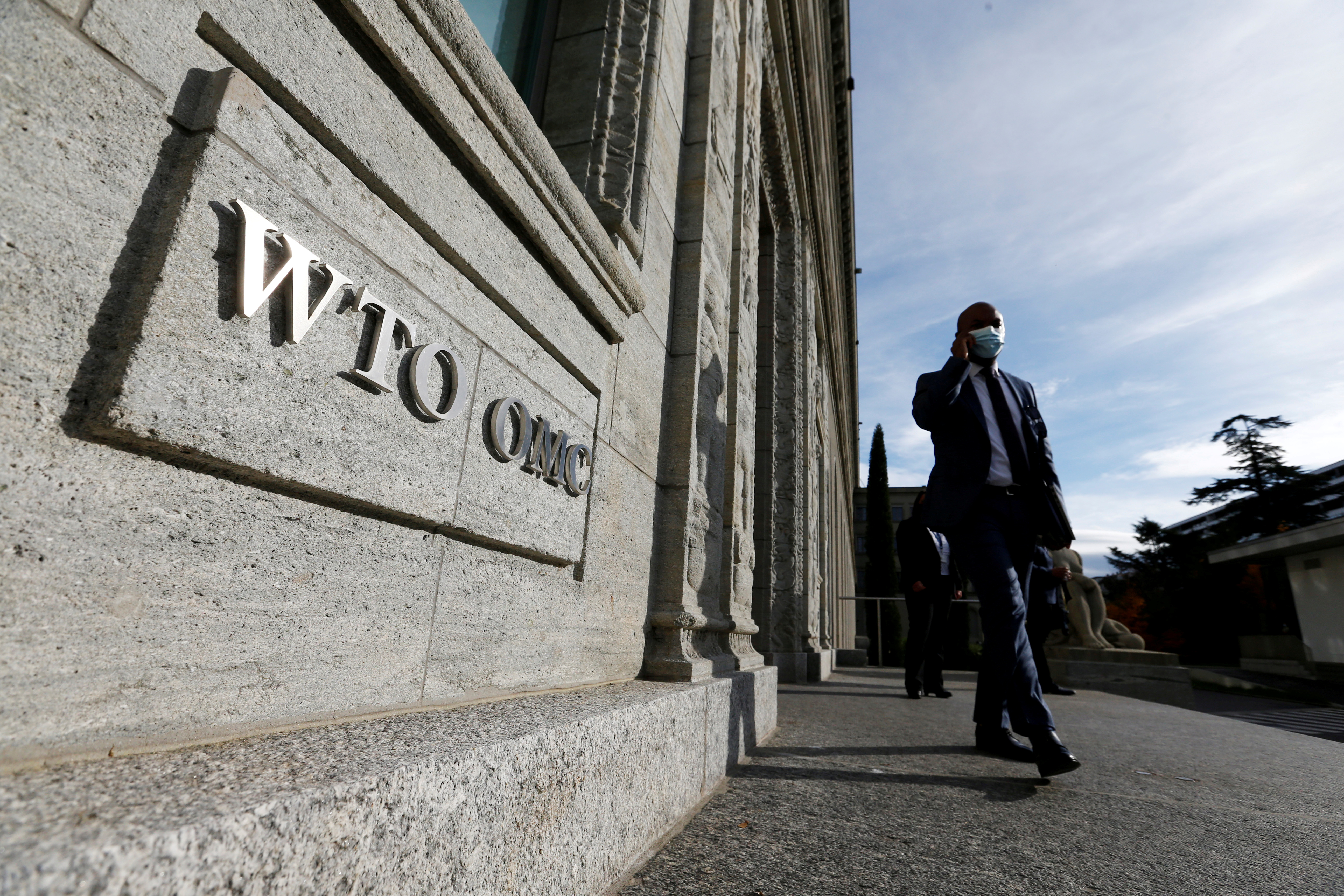 A delegate arrives before a meeting at the World Trade Organization (WTO) in Geneva, Switzerland, October 28, 2020. REUTERS/Denis Balibouse