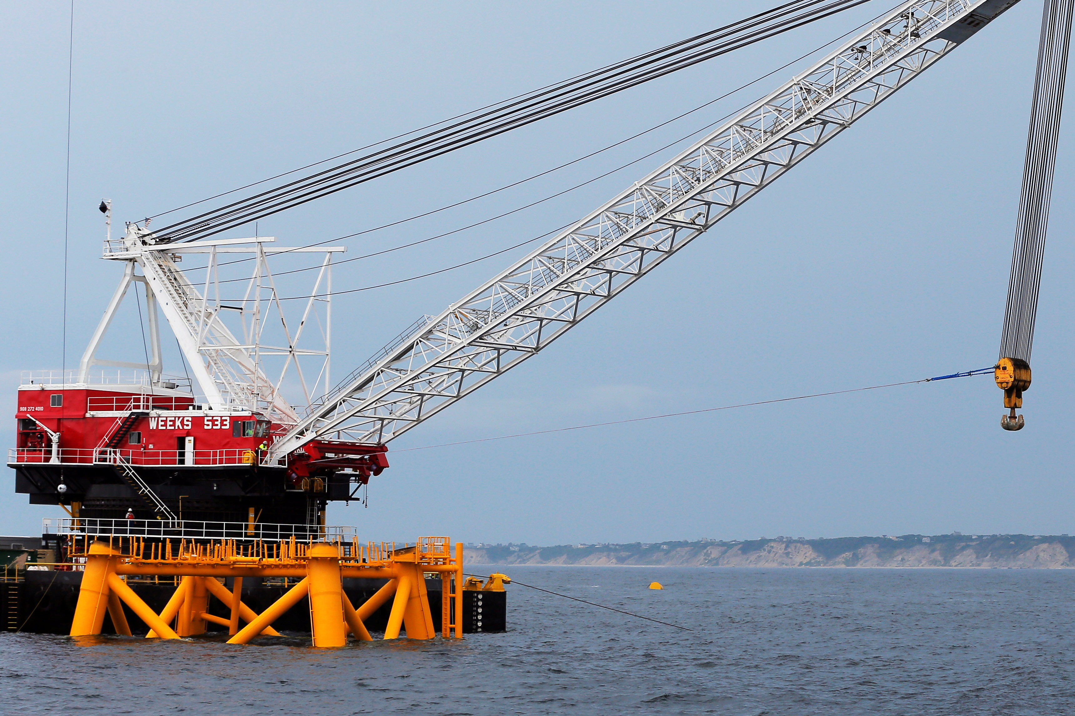 A crane hangs over the first jacket installed to support a turbine for a wind farm in the waters of the Atlantic Ocean off Block Island (rear), Rhode Island July 27, 2015.         REUTERS/Brian Snyder/File Photo
