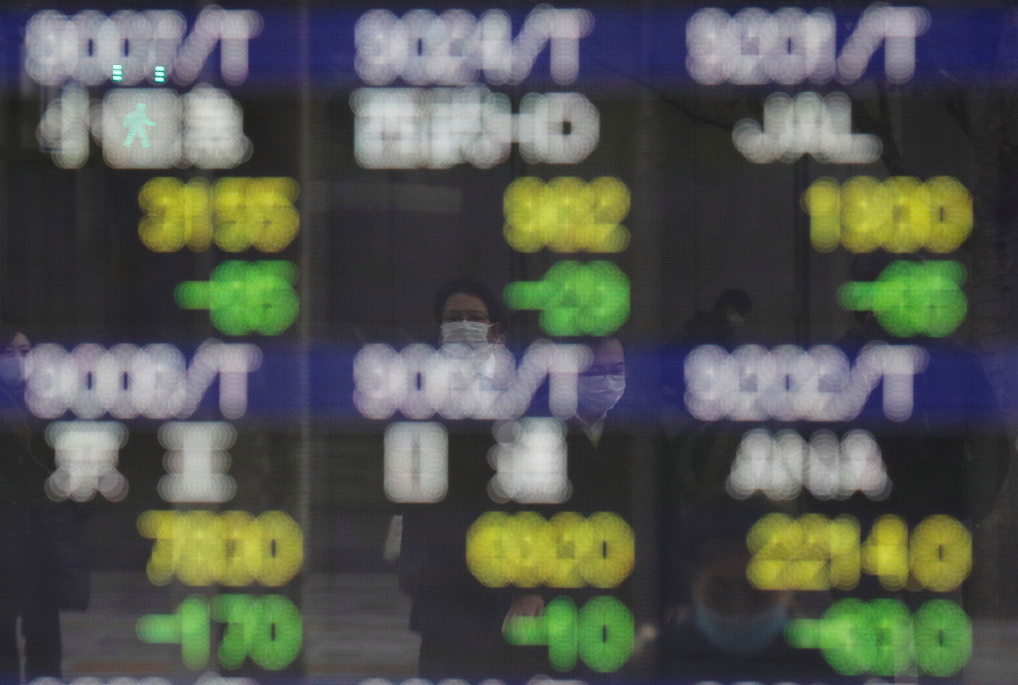 Pedestrians wearing facial masks, following the coronavirus disease (COVID-19) outbreak, are reflected on an electric board showing stock prices outside a brokerage at a business district in Tokyo, Japan, January 4, 2021. REUTERS/Kim Kyung-Hoon/File photo