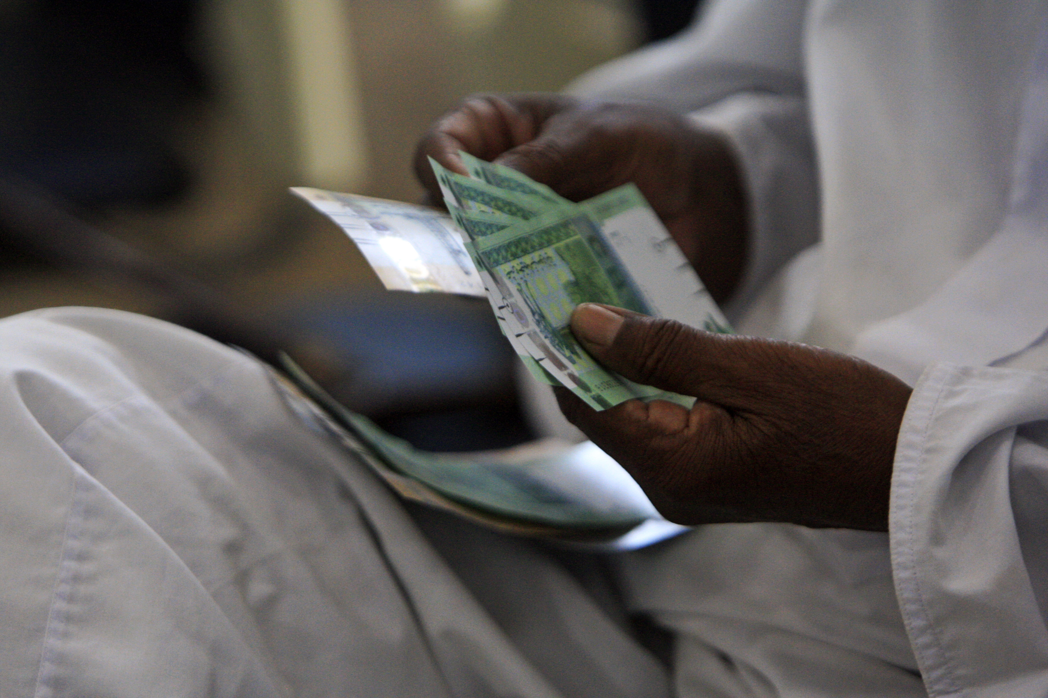 A man counts notes after receiving the new Sudanese currency at a central bank branch in Khartoum July 24, 2011. Sudan on Sunday started circulating its new currency, the central bank said, days after South Sudan started rolling out a currency of its own. REUTERS/ Mohamed Nureldin Abdallah/File Photo