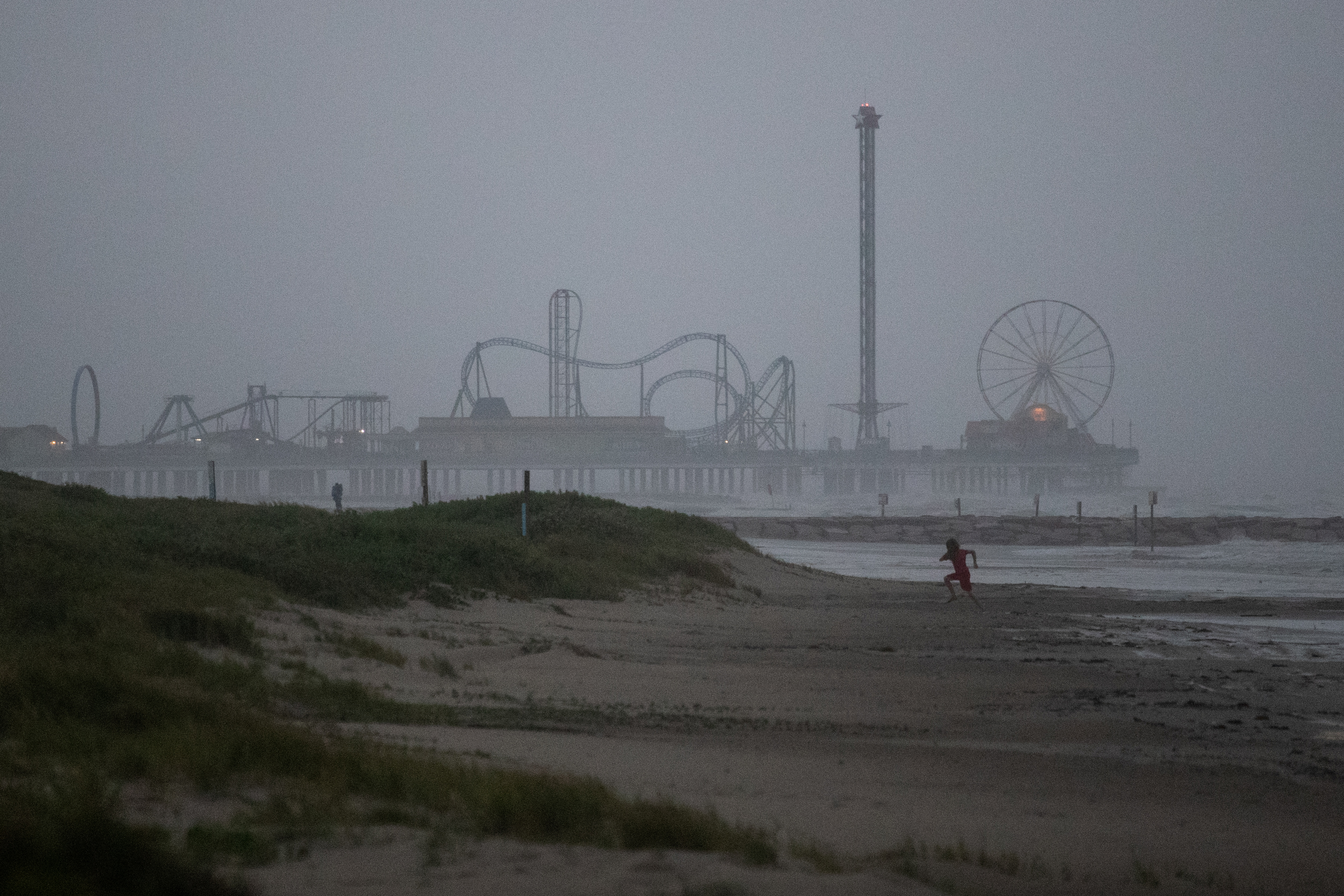 A child plays along the shoreline ahead of the arrival of Tropical Storm Nicholas in Galveston, Texas, U.S., September 13, 2021. REUTERS/Adrees Latif