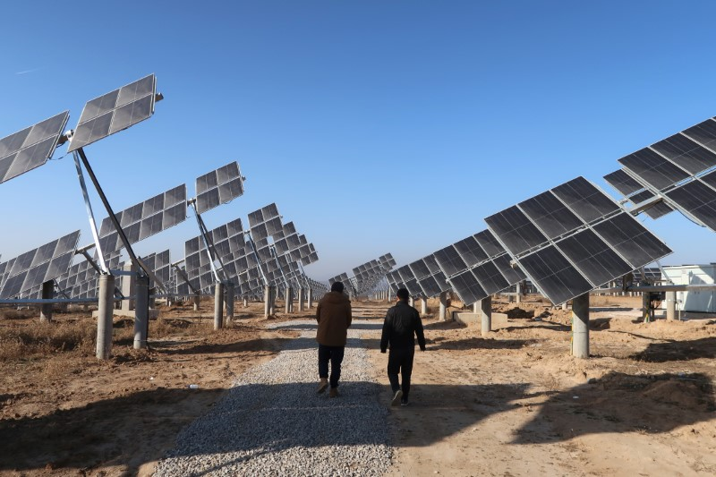 Workers walk at a solar power station in Tongchuan, Shaanxi province, China December 11, 2019. REUTERS/Muyu Xu