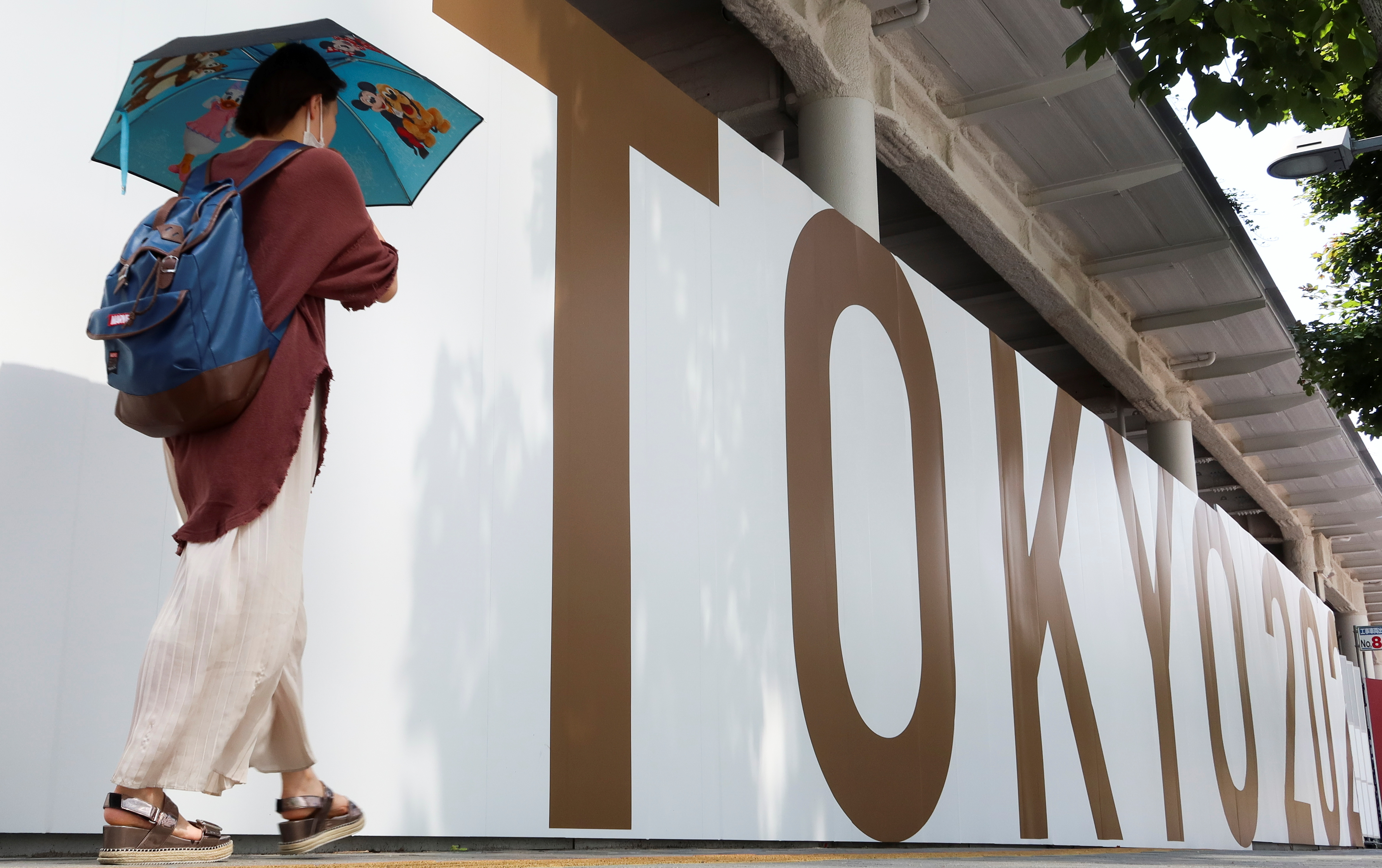 A woman walks outside the security fence of Olympic Stadium (National Stadium) built for Tokyo Olympic Games, that have been postponed to 2021 due to the coronavirus disease (COVID-19) outbreak, in Tokyo, Japan June 11, 2021. REUTERS/Pawel Kopczynski