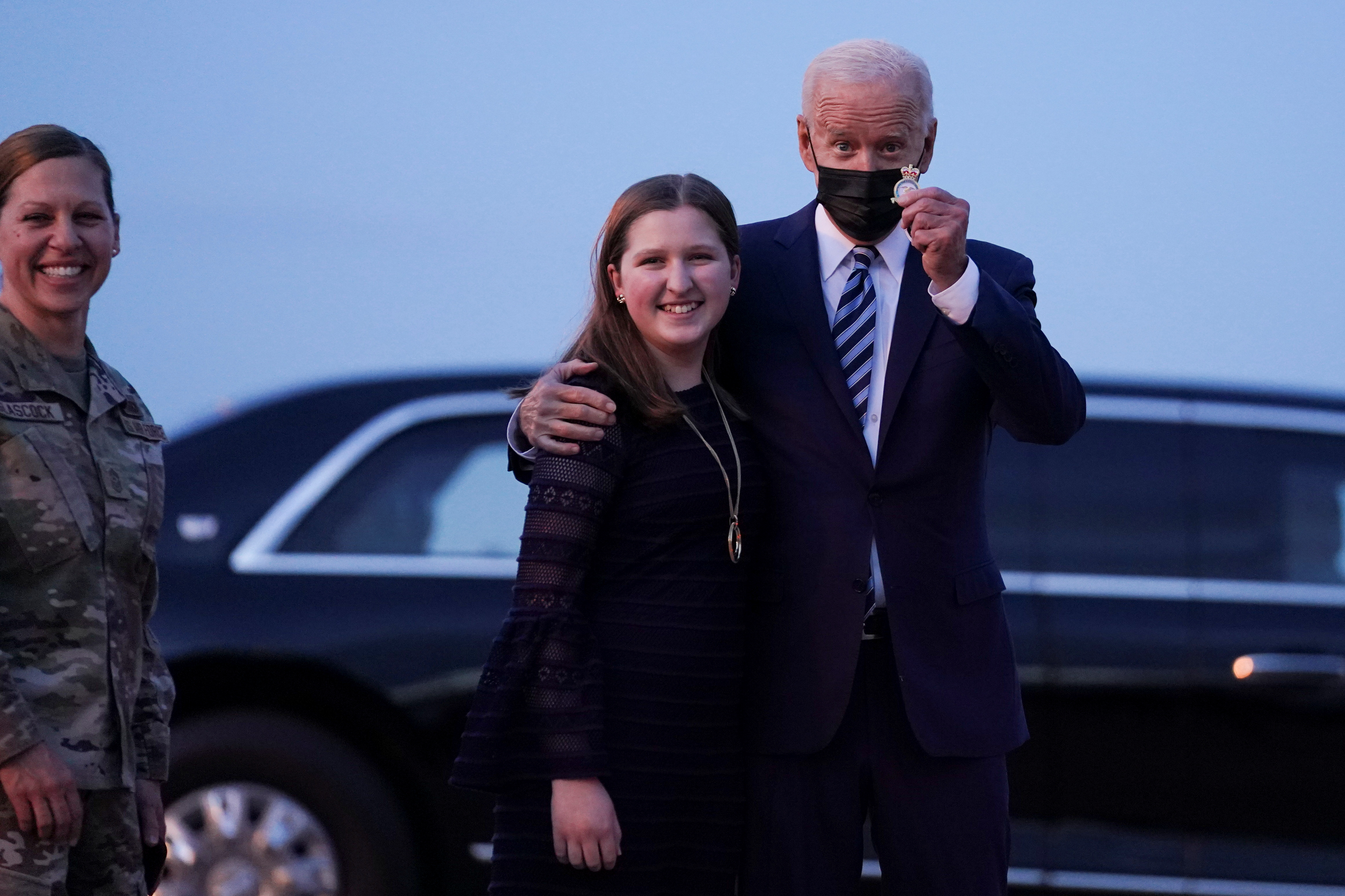 U.S. President Joe Biden holds up a challenge coin as he stands next to Sydney Glascock, Daughter of Command Chief of 100th Air Refueling Wing at RAF Mildenhall, ahead of the G7 Summit, near Mildenhall, Britain June 9, 2021. REUTERS/Kevin Lamarque