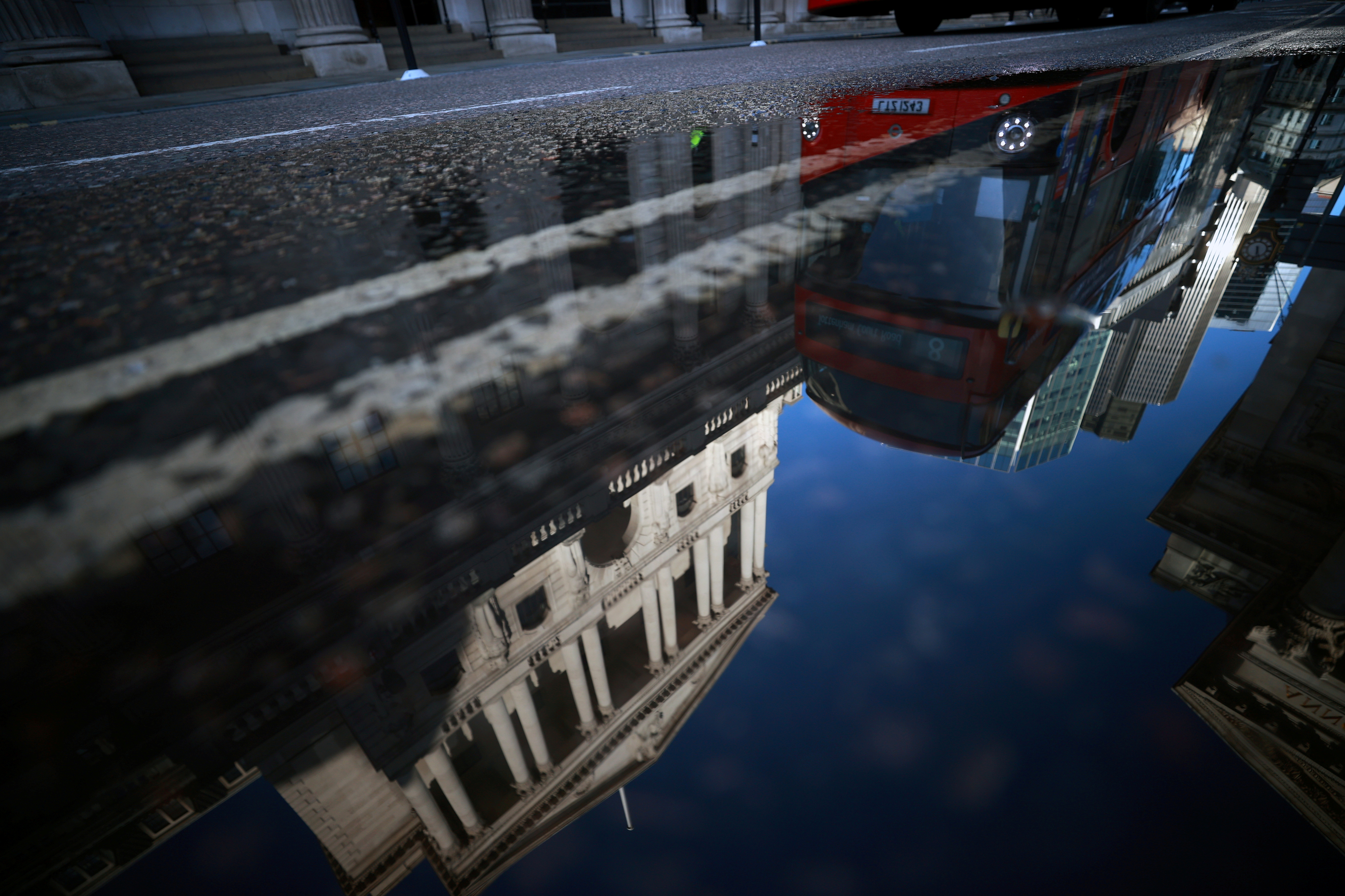 The Bank of England and the City of London financial district are reflected in a puddle, in London, Britain, December 17, 2020. REUTERS/Hannah McKay/File Photo