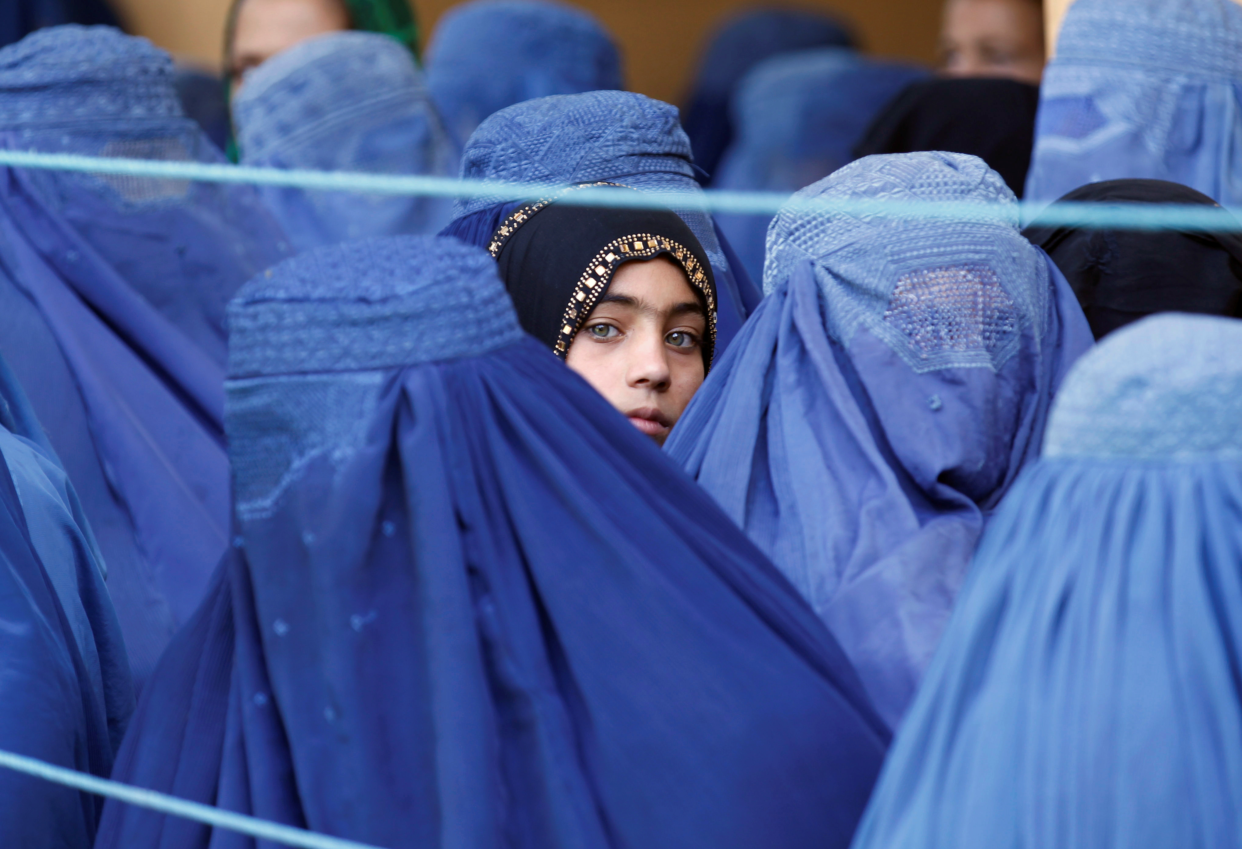 A girl looks on among Afghan women lining up to receive relief assistance, during the holy month of Ramadan in Jalalabad, Afghanistan, June 11, 2017. REUTERS/Parwiz