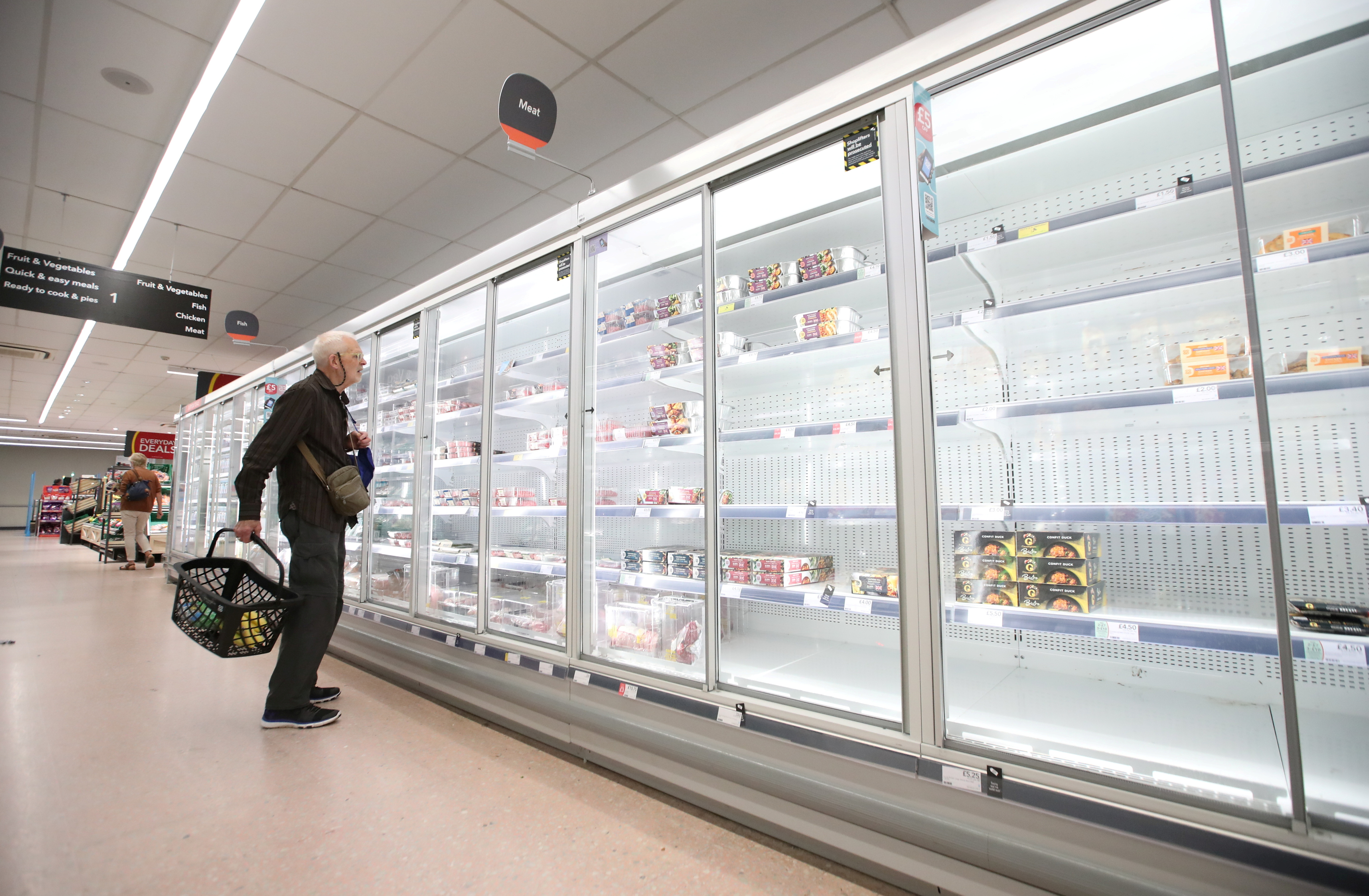A shopper looks at produce and empty shelves of the meat aisle in Co-Op supermarket, Harpenden, Britain, September 22, 2021.  REUTERS/Peter Cziborra