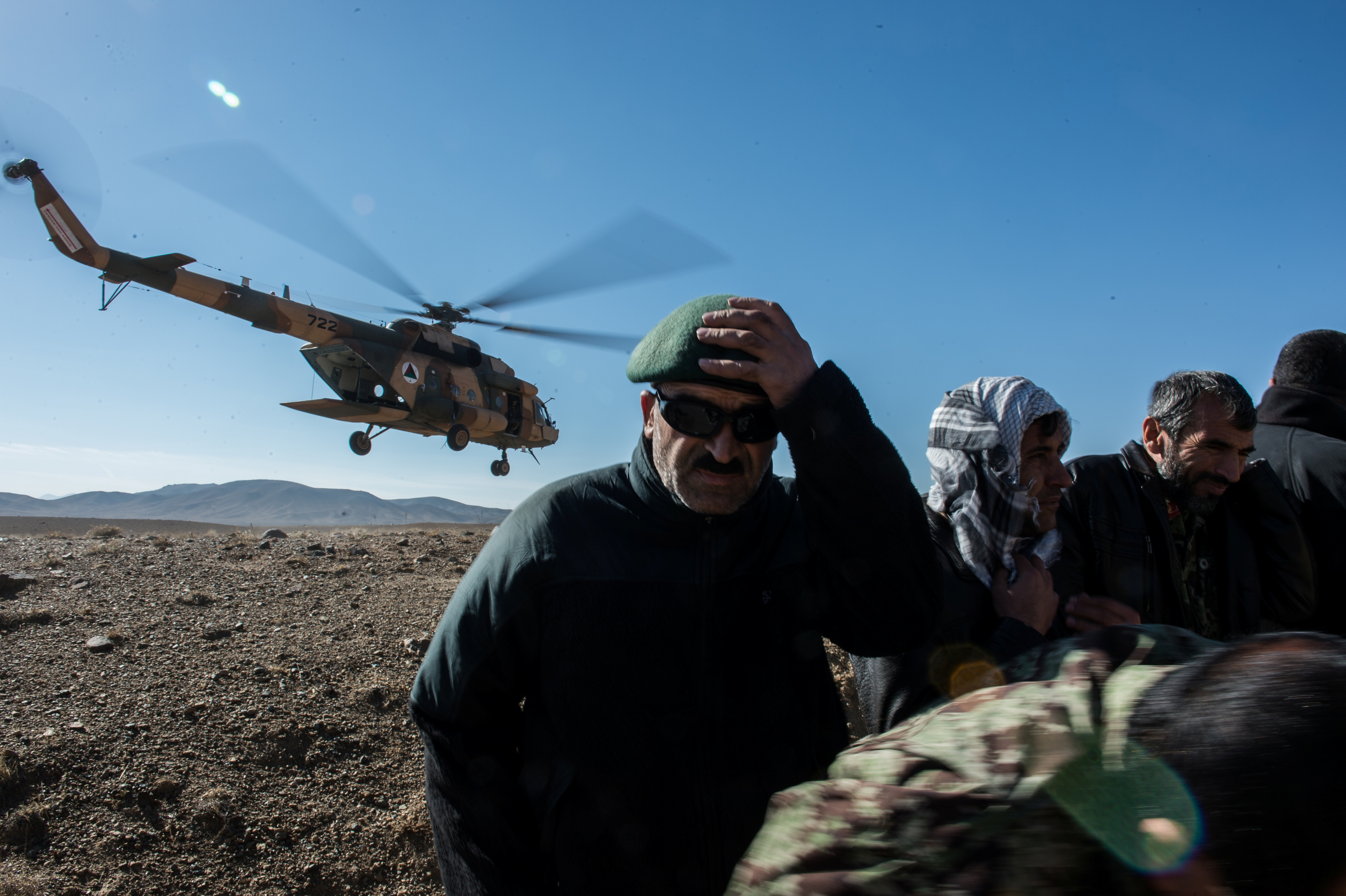 Afghan students take cover as a Mi-17 takes off to provide air cover during the final scenario before graduating from Air Liaison Officer School at Forward Operating Base Hunter range, Afghanistan  November 25, 2014. Picture taken  November 25, 2014. To match Special Report USA-AFGHANISTAN/PILOTS       U.S. Air Force/Staff Sgt. Perry Aston/Handout via REUTERS.