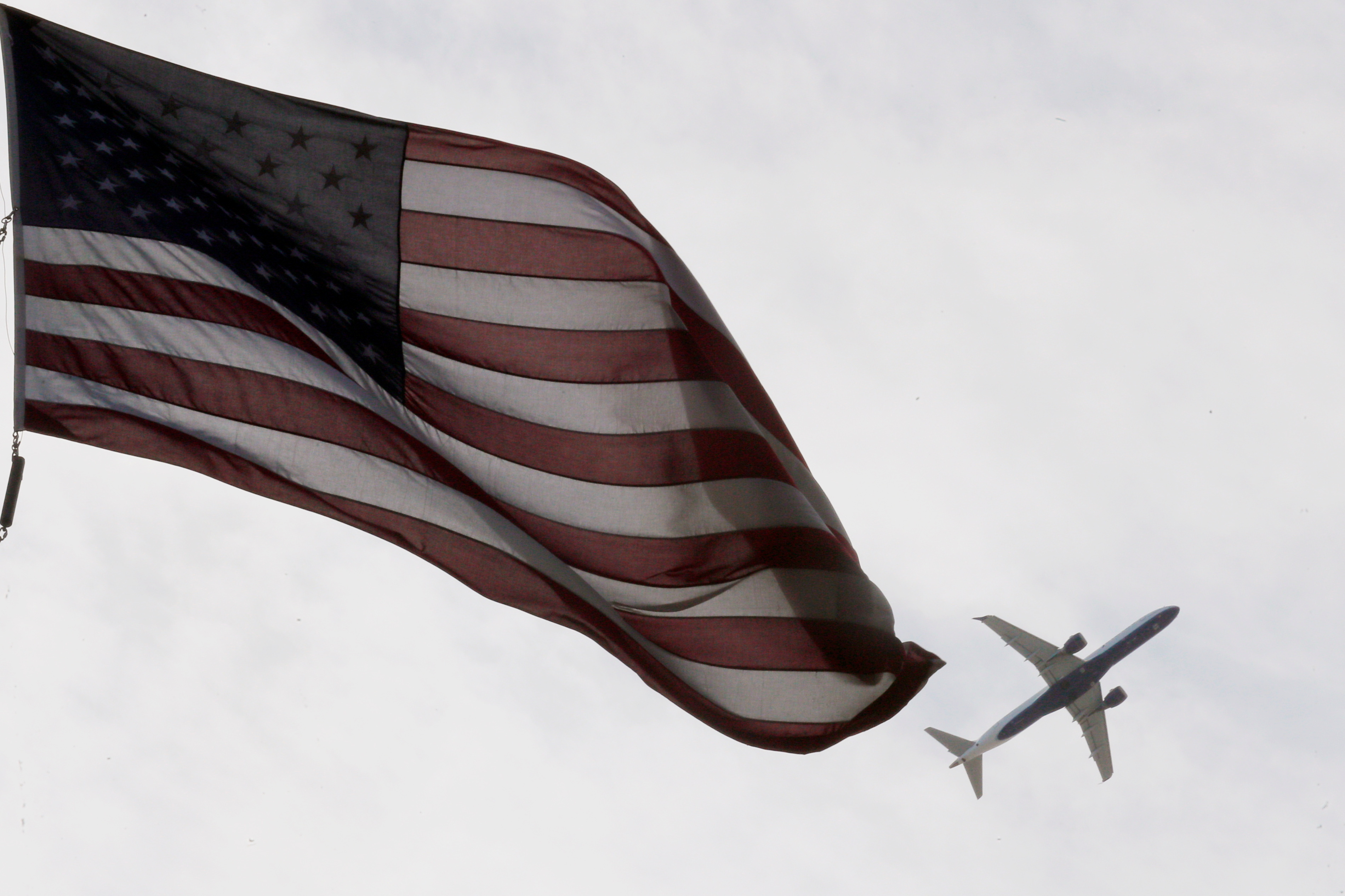 A Delta Airlines flight takes off past a U.S. flag in Boston, Massachusetts, U.S., May 27, 2021.   REUTERS/Brian Snyder/File Photo