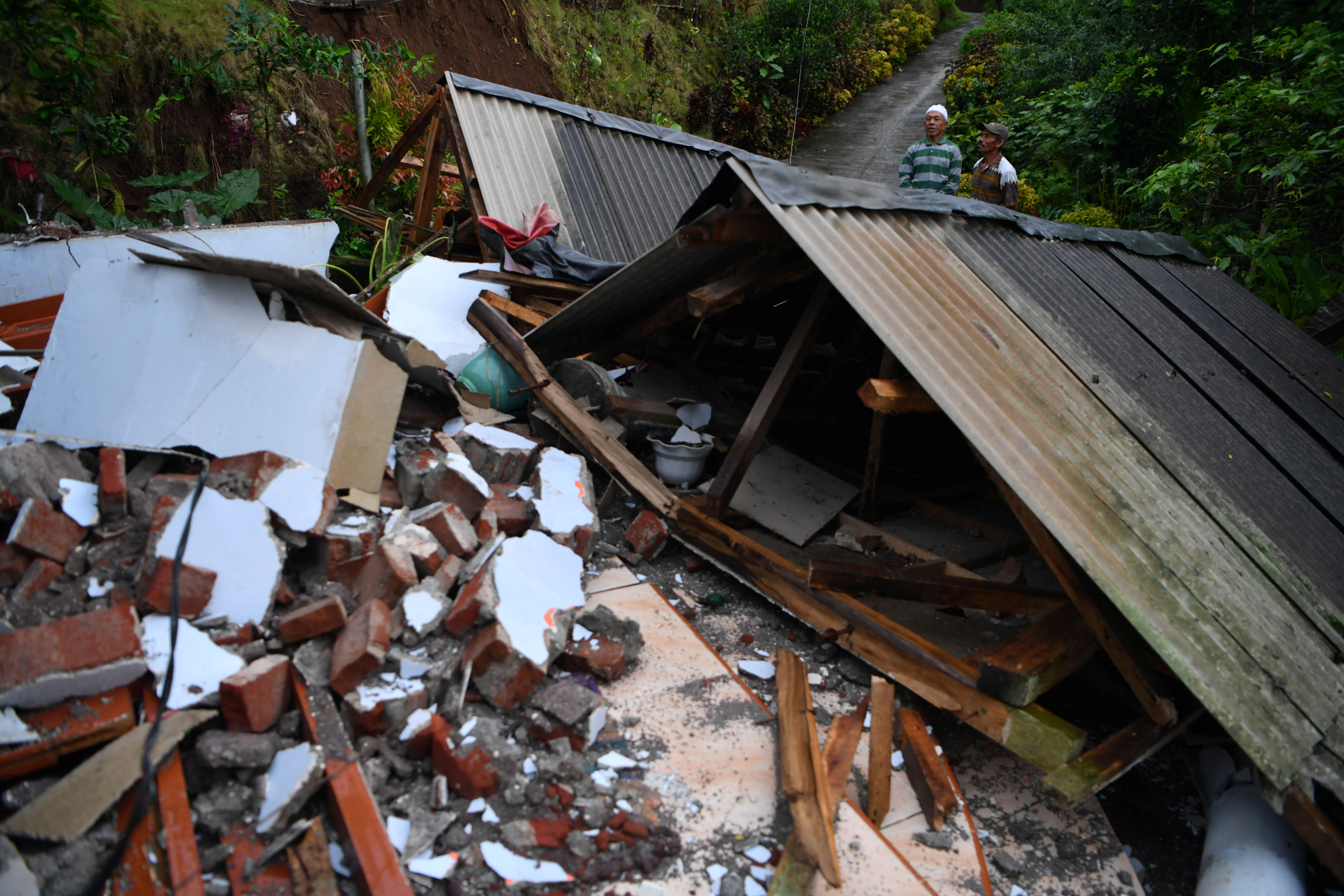 Men stand near a damaged house affected by an earthquake in Lumajang, East Java province, Indonesia April 11, 2021, in this photo taken by Antara Foto. Antara Foto/Zabur Karuru/via Reuters