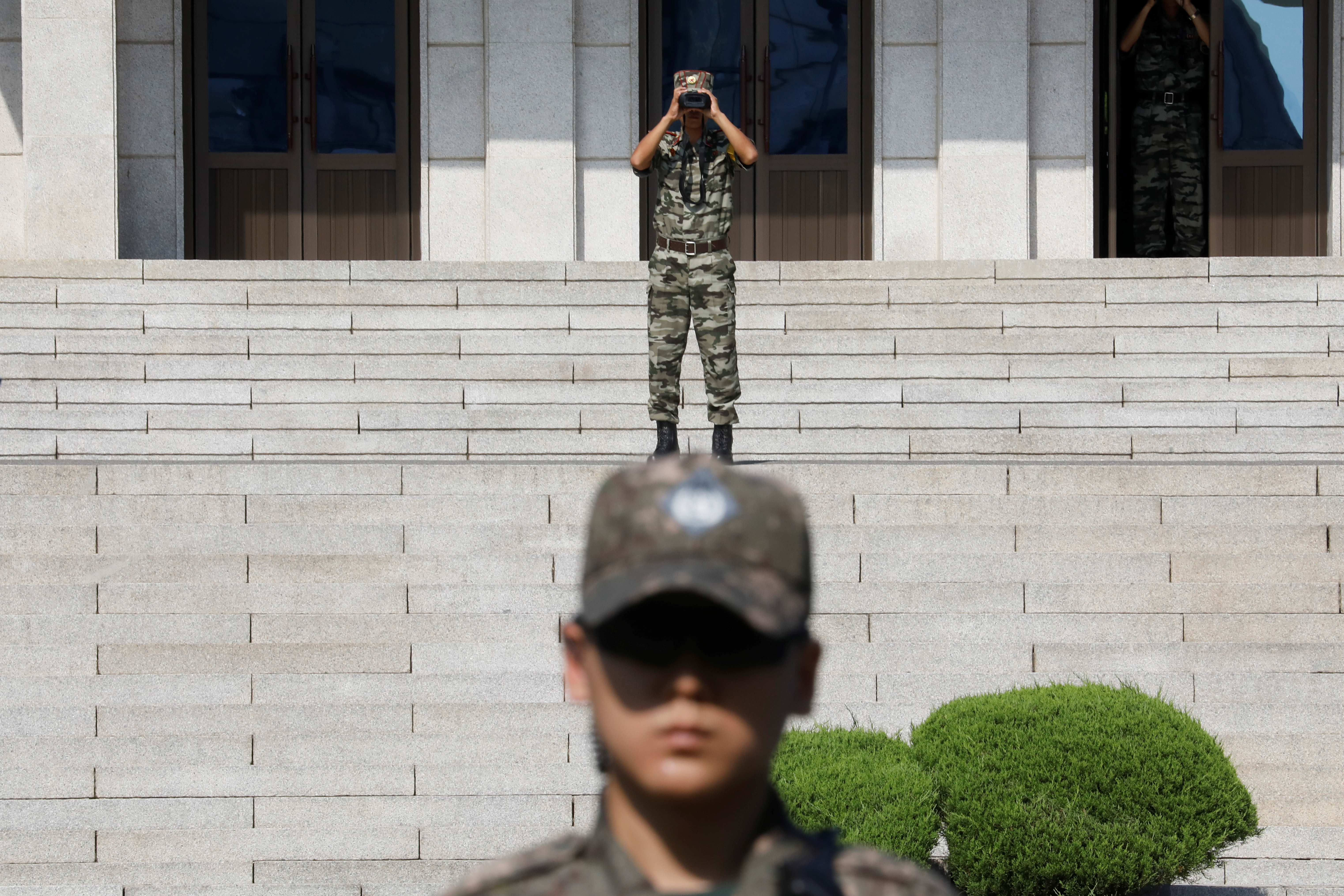 A North Korean soldier looks toward the south as a South Korean soldier stands guard in the truce village of Panmunjom inside the demilitarized zone (DMZ) separating the two Koreas, South Korea, August 28, 2019.    REUTERS/Kim Hong-Ji/Pool
