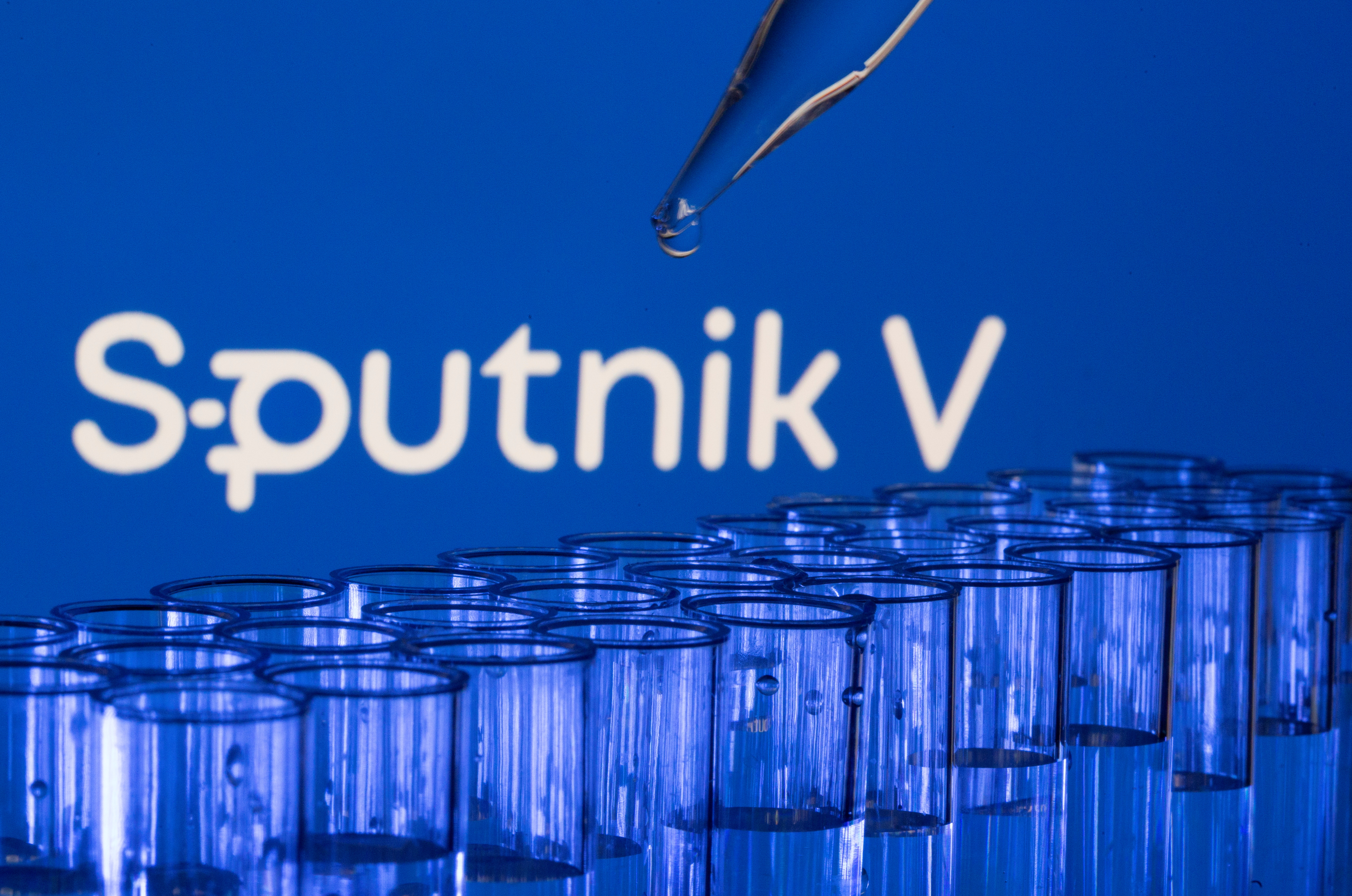 Test tubes are seen in front of a displayed Sputnik V logo in this illustration taken, May 21, 2021. REUTERS/Dado Ruvic/Illustration