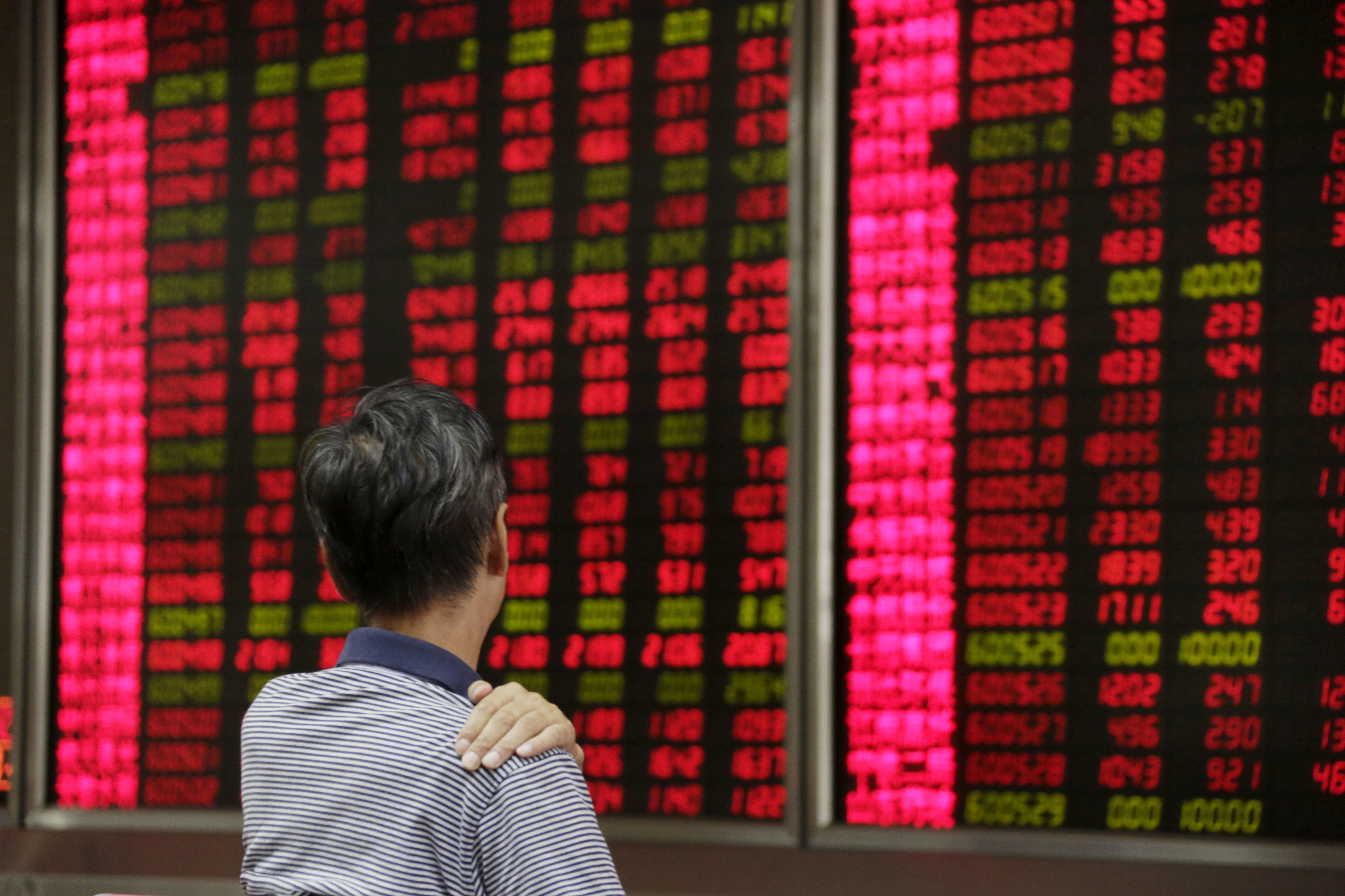 An investor looks at an electronic board showing stock information at a brokerage house in Beijing, August 27, 2015. REUTERS/Jason Lee/File Photo